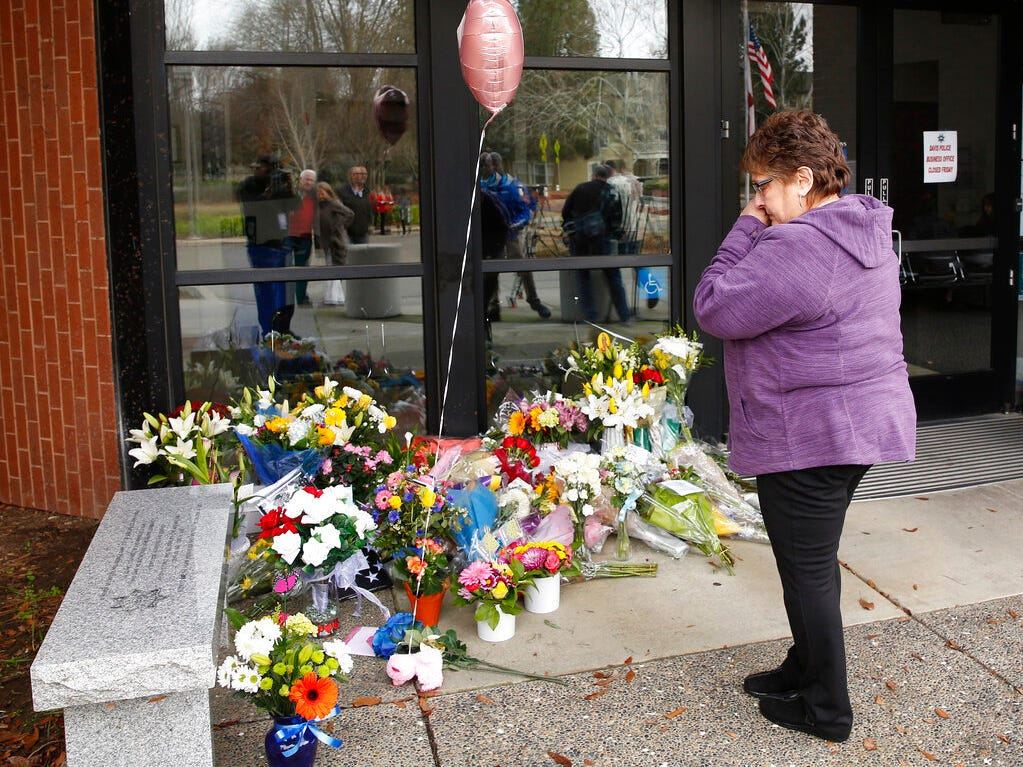 Mary Ann Doerzbacher wipes her eyes after placing flowers on a memorial outside the Davis Police Department for slain Davis Police Officer Natalie Corona, Friday, Jan. 11, 2019, in Davis, Calif. Corona, 22, who had been on the job only a few weeks was shot and killed, Thursday, by a suspect who opened fire as she was investigating a three-car crash. The suspect was later found dead from a self-inflicted gunshot, following a standoff with officers.