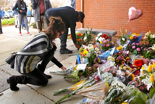 Mourners place flowers on a memorial outside the Davis Police Department for slain Davis Police Officer Natalie Corona, Friday, Jan. 11, 2019, in Davis, Calif. Corona, 22, who had been on the job only a few weeks was shot and killed, Thursday, by a suspect who opened fire as she was investigating a three-car crash. The suspect was later found dead from a self-inflicted gunshot, following a standoff with officers.
