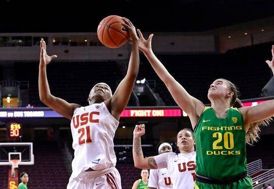 Southern California's Aliyah Mazyck, left, and Oregon's Sabrina Ionescu reach for a rebound during the second half of an NCAA college basketball game Friday, Jan. 11, 2019, in Los Angeles. Oregon won 93-53. (AP Photo/Mark J. Terrill)