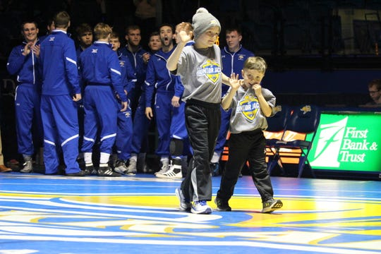 A pair of young Jackrabbit fans lead the SDSU wrestling team onto the mat before their dual with Northern Iowa Friday night at Frost Arena