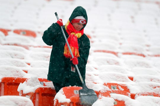 A groundskeeper brushes snow off of seats at Arrowhead Stadium before an NFL divisional football playoff game against the Indianapolis Colts in Kansas City, Mo., Saturday, Jan. 12, 2019.