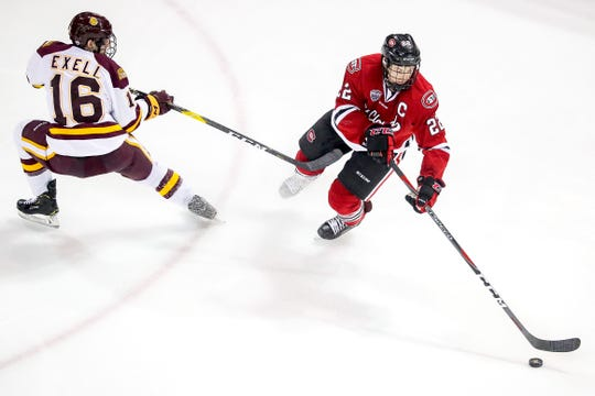 Forward Billy Exell (16) of the Minnesota Duluth Bulldogs pressures defenseman Jimmy Schuldt (22) of the St. Cloud State Huskies during Friday's game at Amsoil Arena in Duluth, Minn.