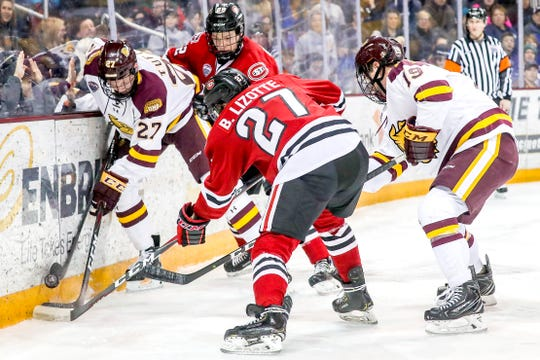 Forward Riley Tufte (27) of the Minnesota Duluth Bulldogs competes with forward Blake Lizotte (27) and defenseman Jimmy Schuldt (22) of the St. Cloud State Huskies for the puck during Friday's game at Amsoil Arena in Duluth, Minn.