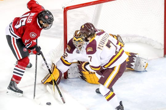 Forward Micah Miller (15) of the St. Cloud State Huskies puts the puck on goal against goaltender Hunter Shepard (32) and defenseman Scott Perunovich (7) of the Minnesota Duluth Bulldogs during Friday's game at Amsoil Arena in Duluth, Minn.