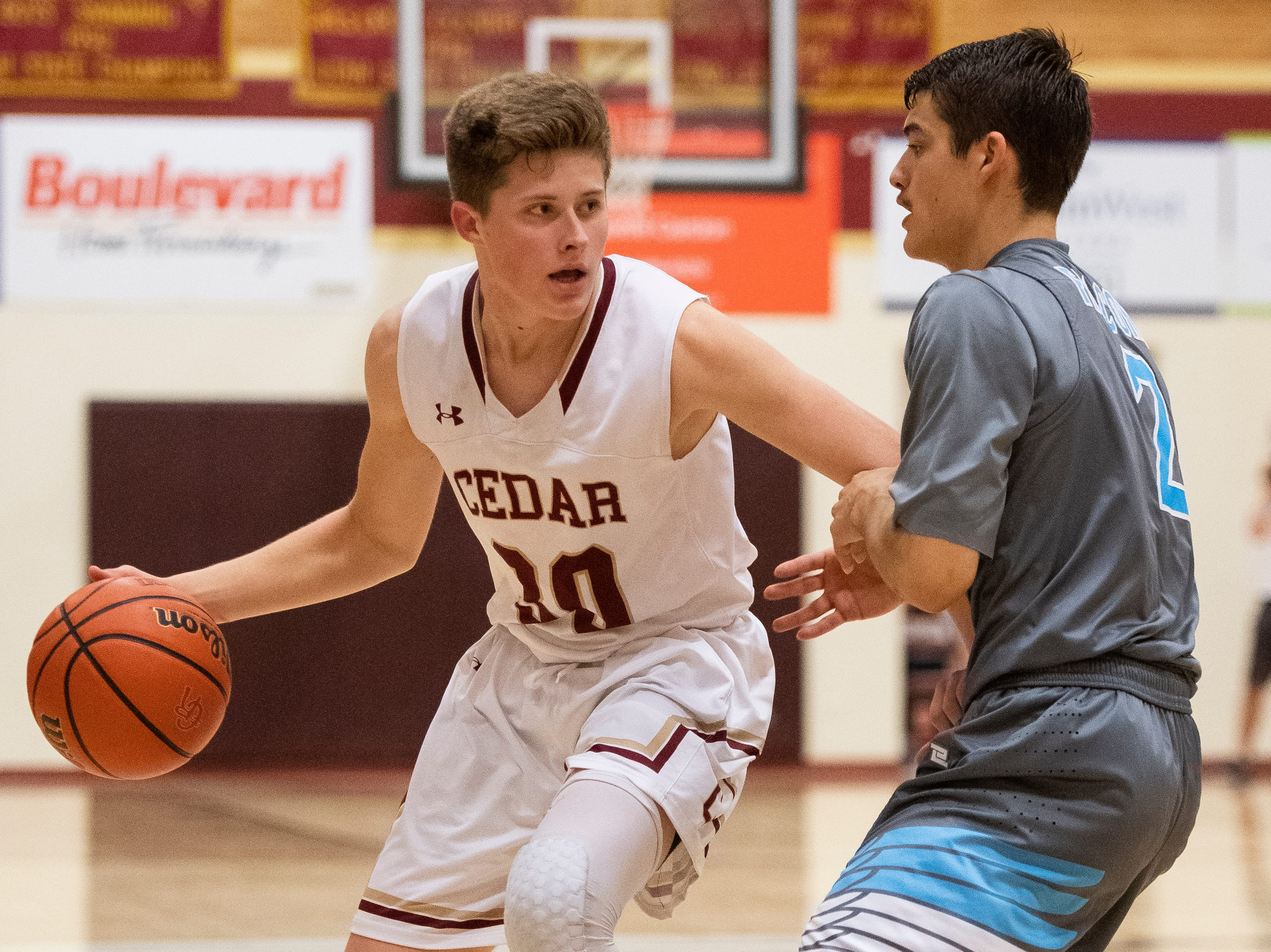 Cedar High School senior Ryan Kite (10) tries to get around Canyon View High School senior Mason Lyman (2) at CHS Friday, January 11, 2019. Canyon View won, 61-56.