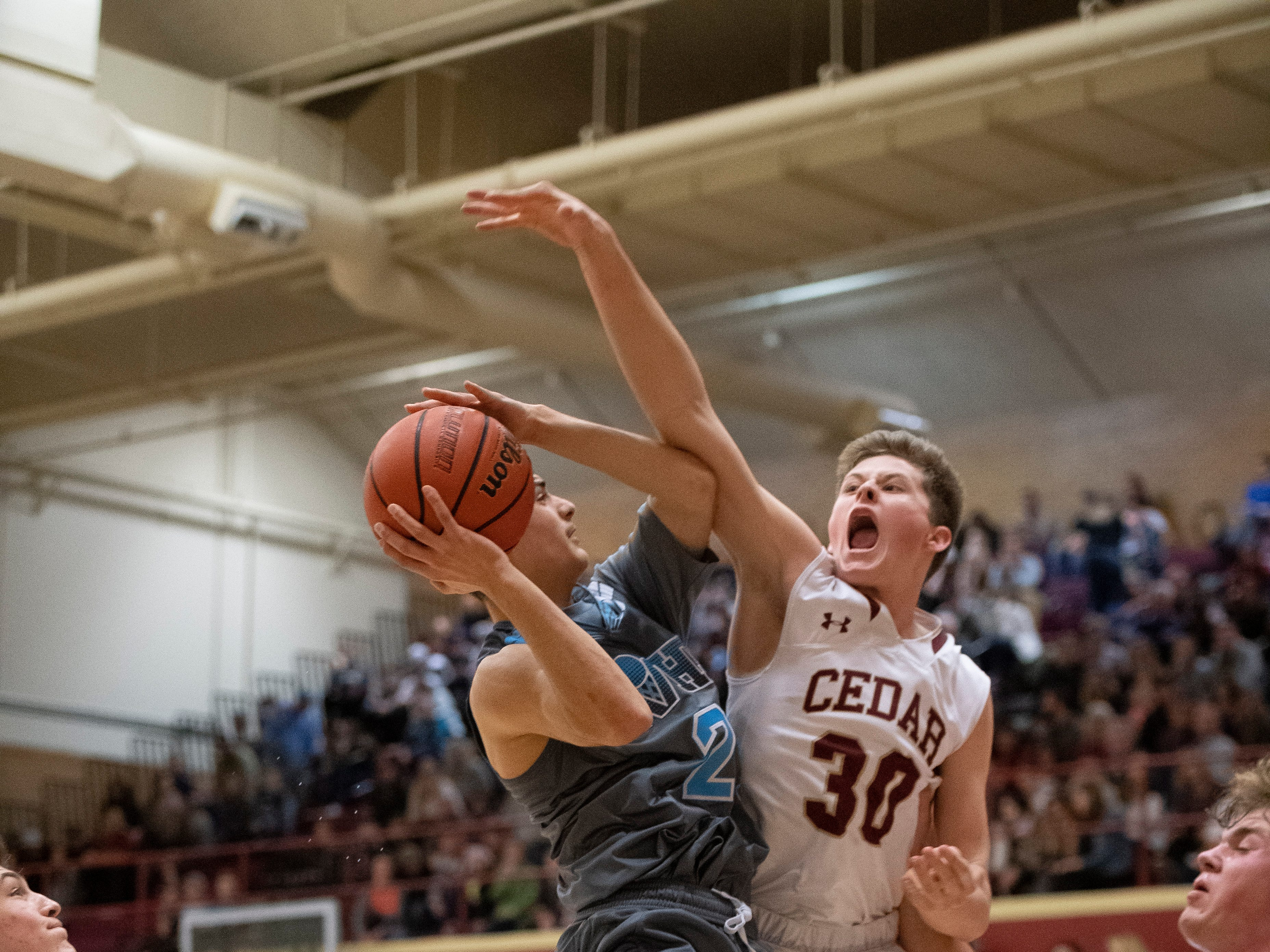Cedar High School junior Landon Barney (30) tries to block the shot of Canyon View High School senior Mason Lyman (2) at CHS Friday, January 11, 2019. Canyon View won, 61-56.