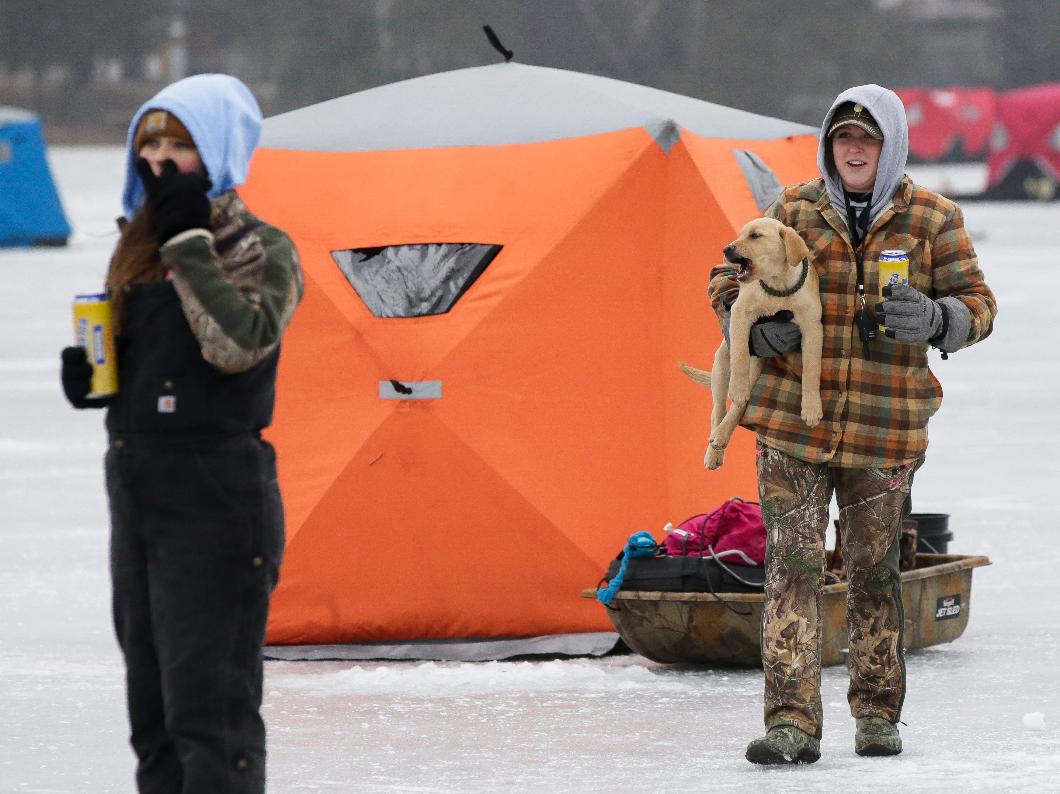 Natalie Widder carries her puppy on Saturday, January 12, 2019, during the Rosholt Blizzard Busters Fisheree at Lake Helen outside Rosholt, Wis.Tork Mason/USA TODAY NETWORK-Wisconsin