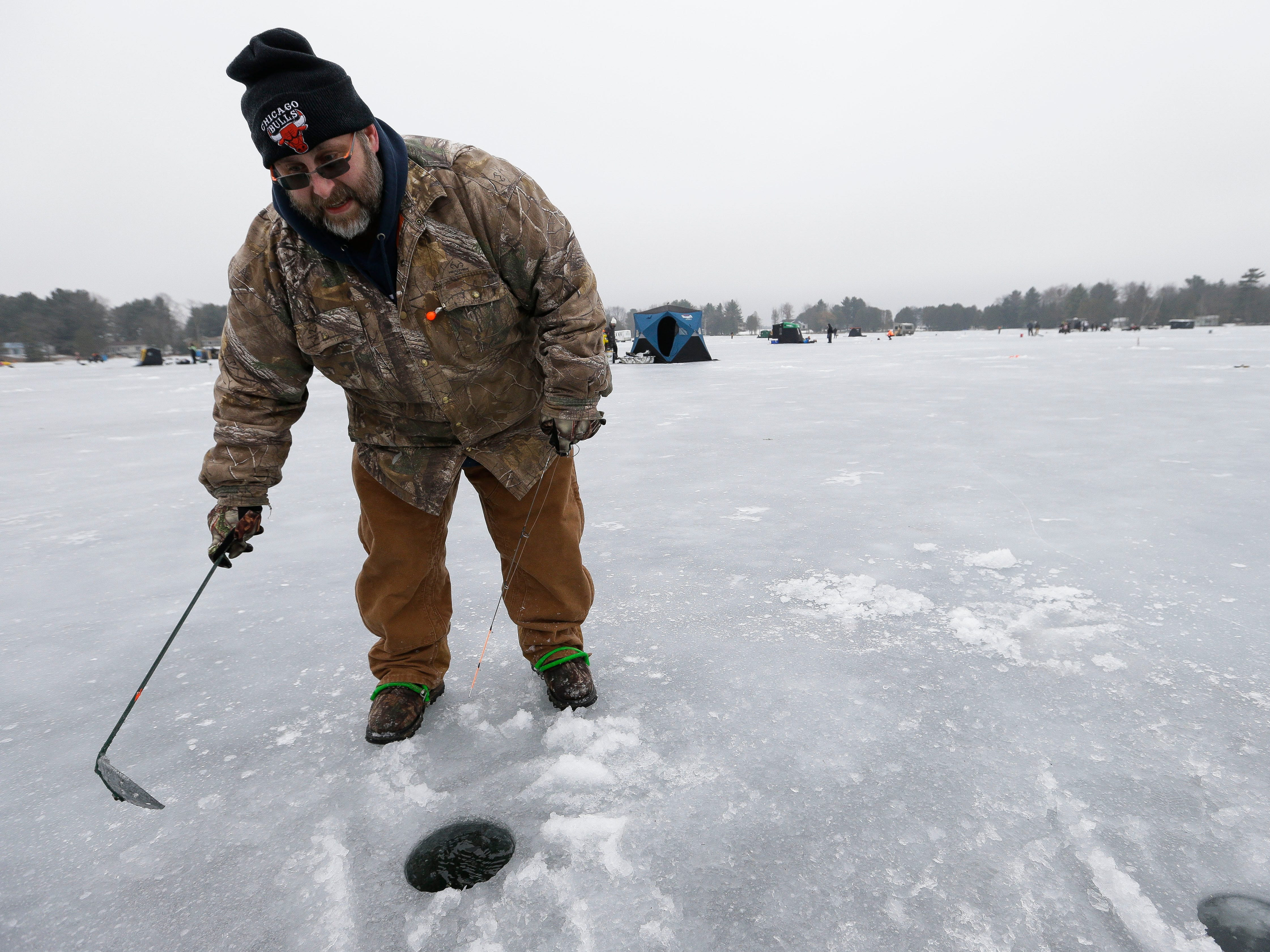 Steve Steinhauer scoops fresh ice out of his fishing hole on Saturday, January 12, 2019, during the Rosholt Blizzard Busters Fisheree at Lake Helen outside Rosholt, Wis.Tork Mason/USA TODAY NETWORK-Wisconsin