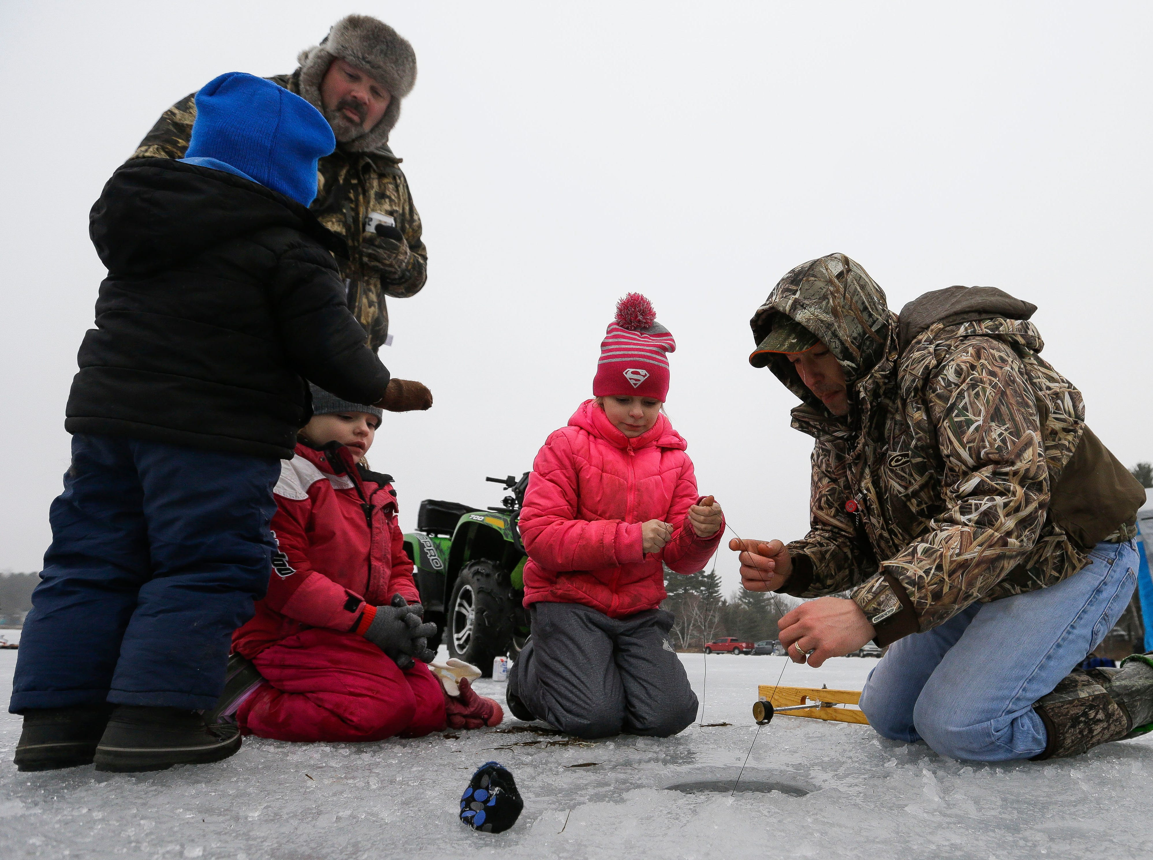 Jeremy Becker helps Ayranna and Jazzy Crowell pull their line on Saturday, January 12, 2019, during the Rosholt Blizzard Busters Fisheree at Lake Helen outside Rosholt, Wis.Tork Mason/USA TODAY NETWORK-Wisconsin