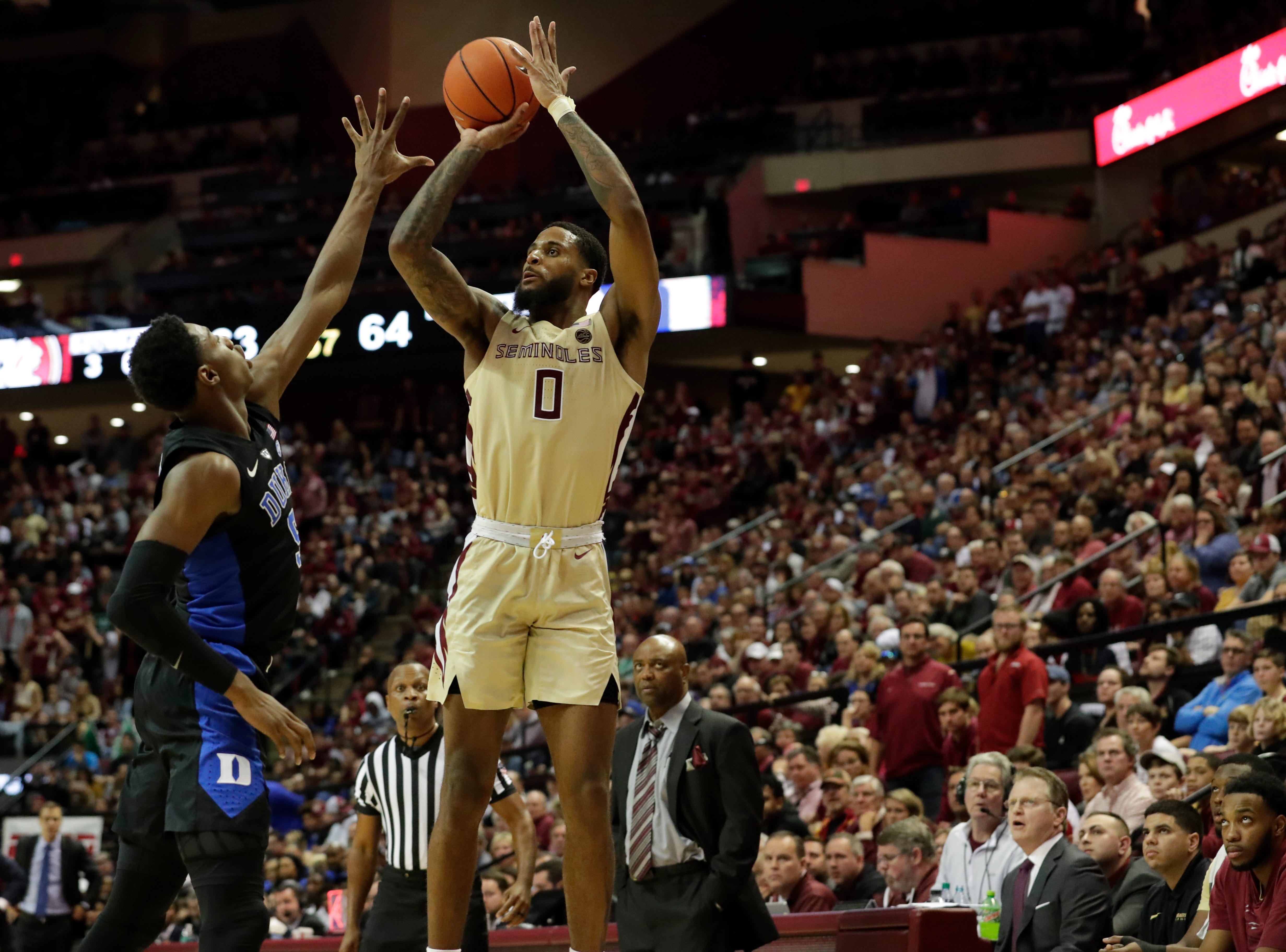Florida State Seminoles forward Phil Cofer (0) shoots for three over his defender's reach. Ranked 13 in the ACC, the Florida State Seminoles host the number 1 team, the Duke Blue Devils, at the Tucker Civic Center, Saturday, Jan. 12, 2019.