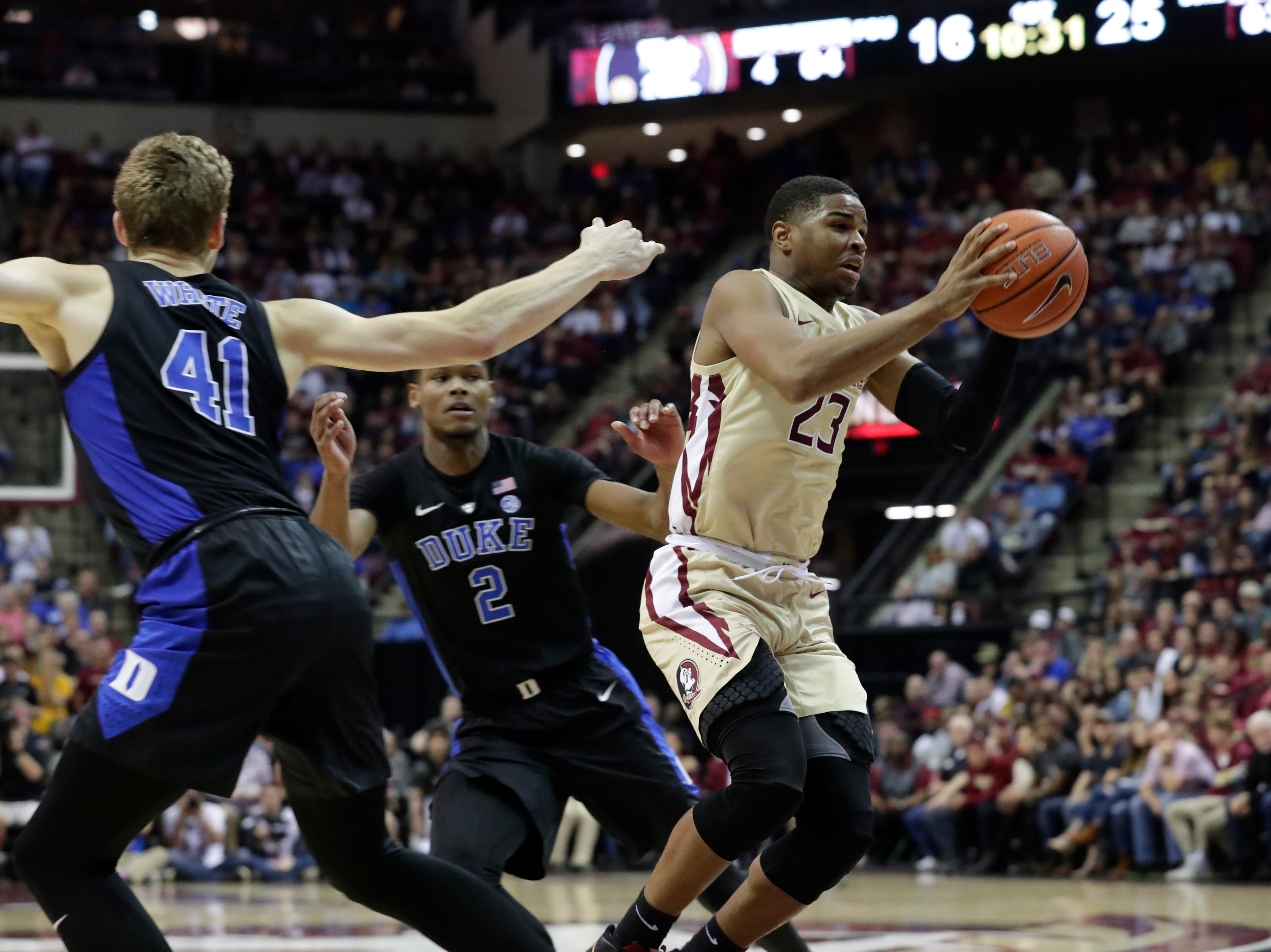 Ranked 13 in the ACC, the Florida State Seminoles host the number 1 team, the Duke Blue Devils, at the Tucker Civic Center, Saturday, Jan. 12, 2019. Florida State Seminoles guard M.J. Walker (23) makes his way around Duke Blue Devils forward Jack White (41) and Duke Blue Devils forward Cam Reddish (2) to drive the ball to the hoop.