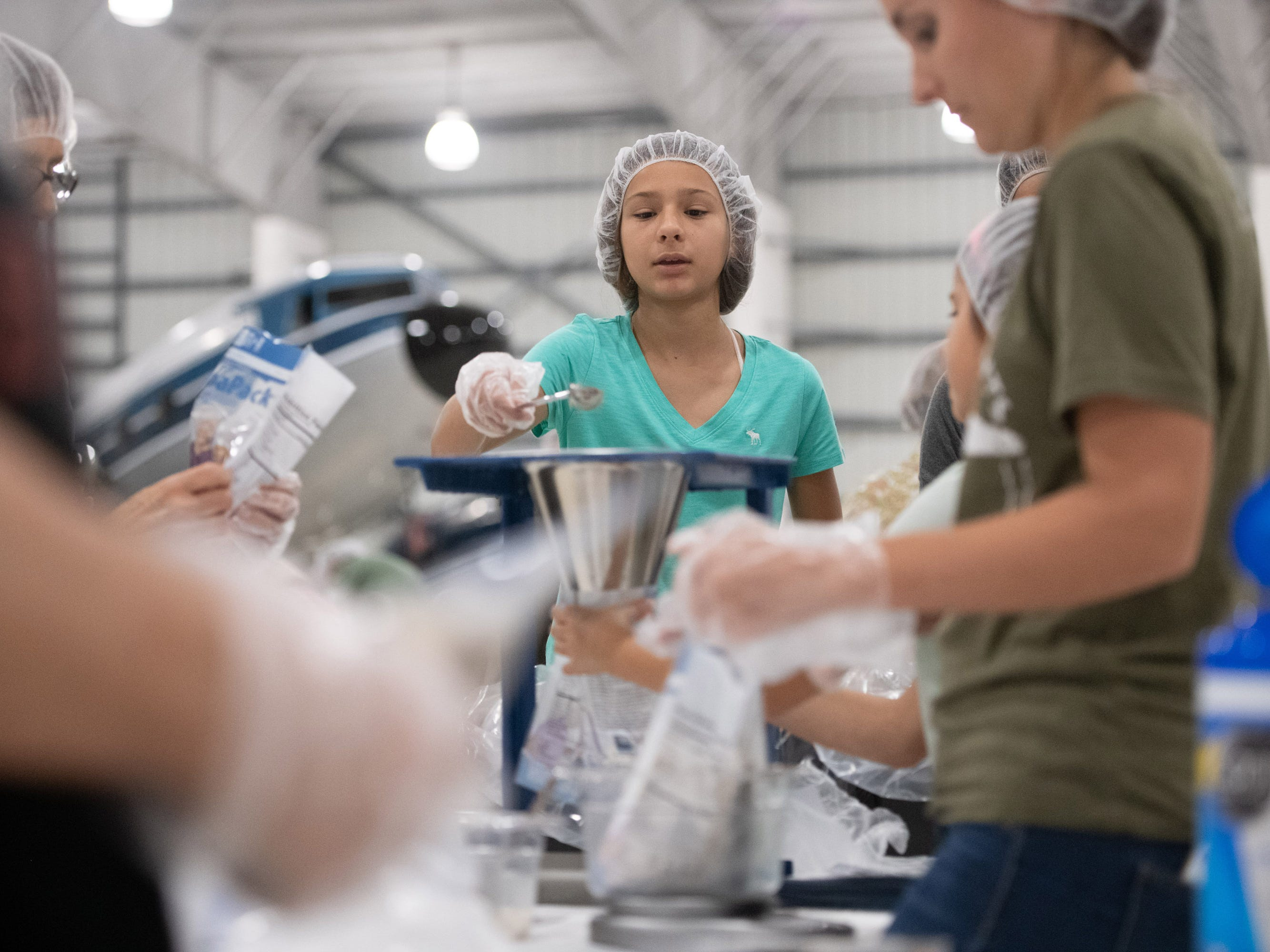 Community volunteers help pack food designed especially for starving children for Missionary Flights International, who is partnering with Feed My Starving Children to serve missionaries in Haiti, the Dominican Republic, the Bahamas, and in events of disaster throughout the Caribbean, on Saturday, Jan. 12, 2019, at Missionary Flights International in Fort Pierce.