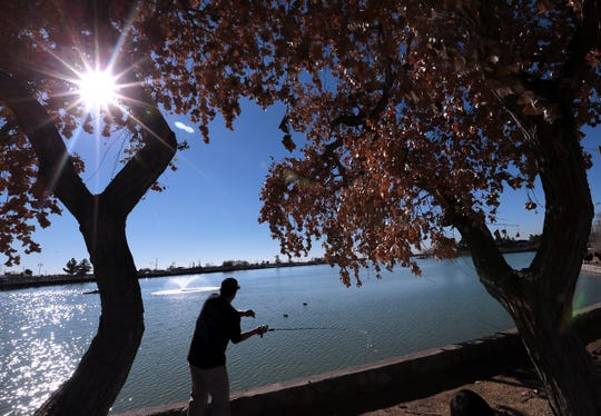Josue Chavez casts his line beneath a pair of cottonwoods Saturday, Jan. 12, 2019, at Ascarate Lake. El Paso County Parks and Recreation hosted its Winter Trout Reel In Tournament. Trophies were awarded for the top three anglers.