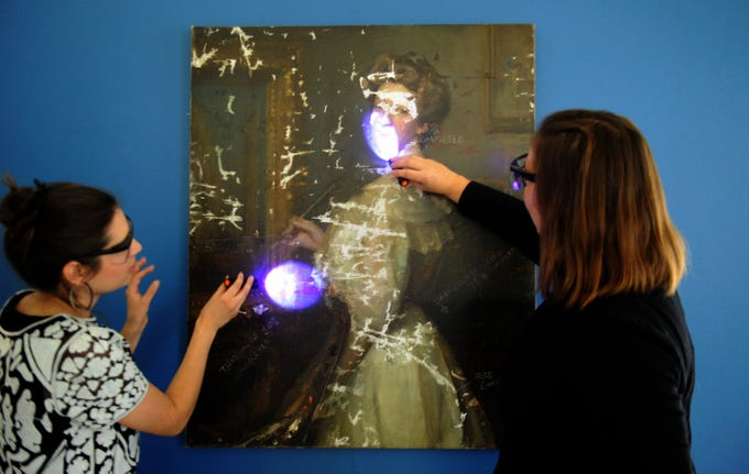 """Rachel Schmid (left), curator of the William Rolland Gallery of Fine Art, and  Katherine Hoffman, the John Stauffer professor of analytical chemistry, look at a painting by an unknown artist under UV light to show the different layers. The painting is part of """"Traces: Revealing Secrets in Art and History"""" at the California Lutheran University gallery. The exhibit was created in partnership with the university's chemistry department and Hoffman will use it in her """"Chemical Investigations of Art"""" class during the spring semester."""