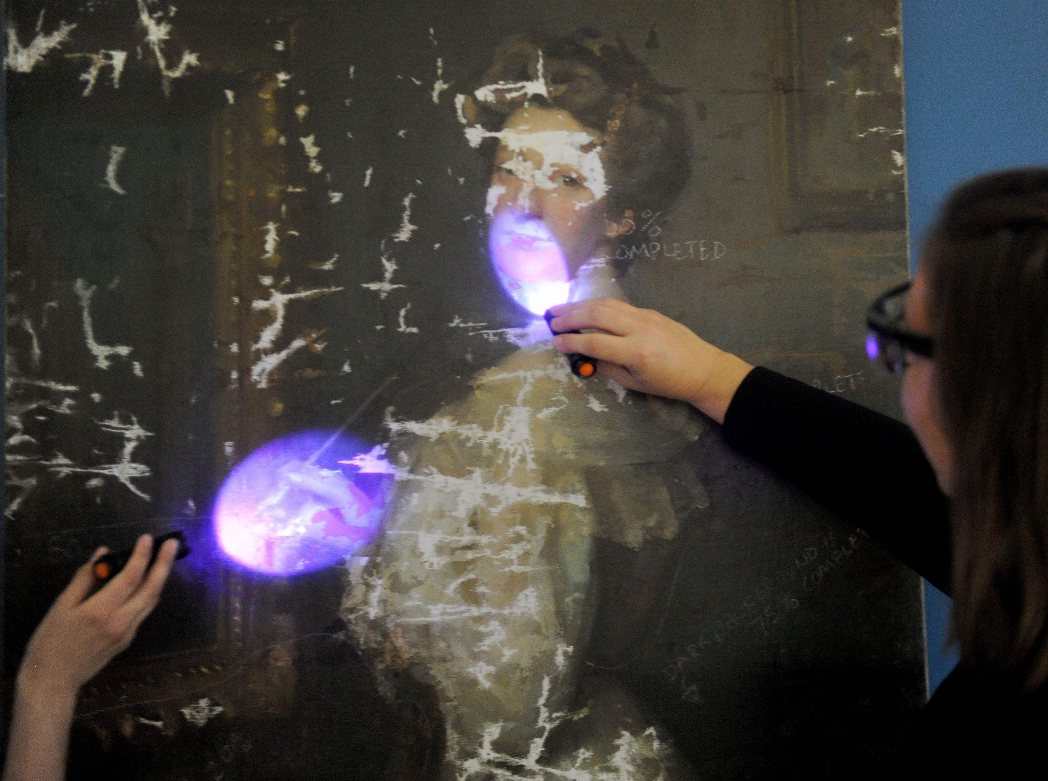 """Rachel Schmid (left), curator of the William Rolland Gallery of Fine Art, and  Katherine Hoffman, the John Stauffer professor of analytical chemistry, look at a piece of art under UV light to show the different layers of paint. It is part of the exhibit, """"Traces: Revealing Secrets in Art and History."""""""