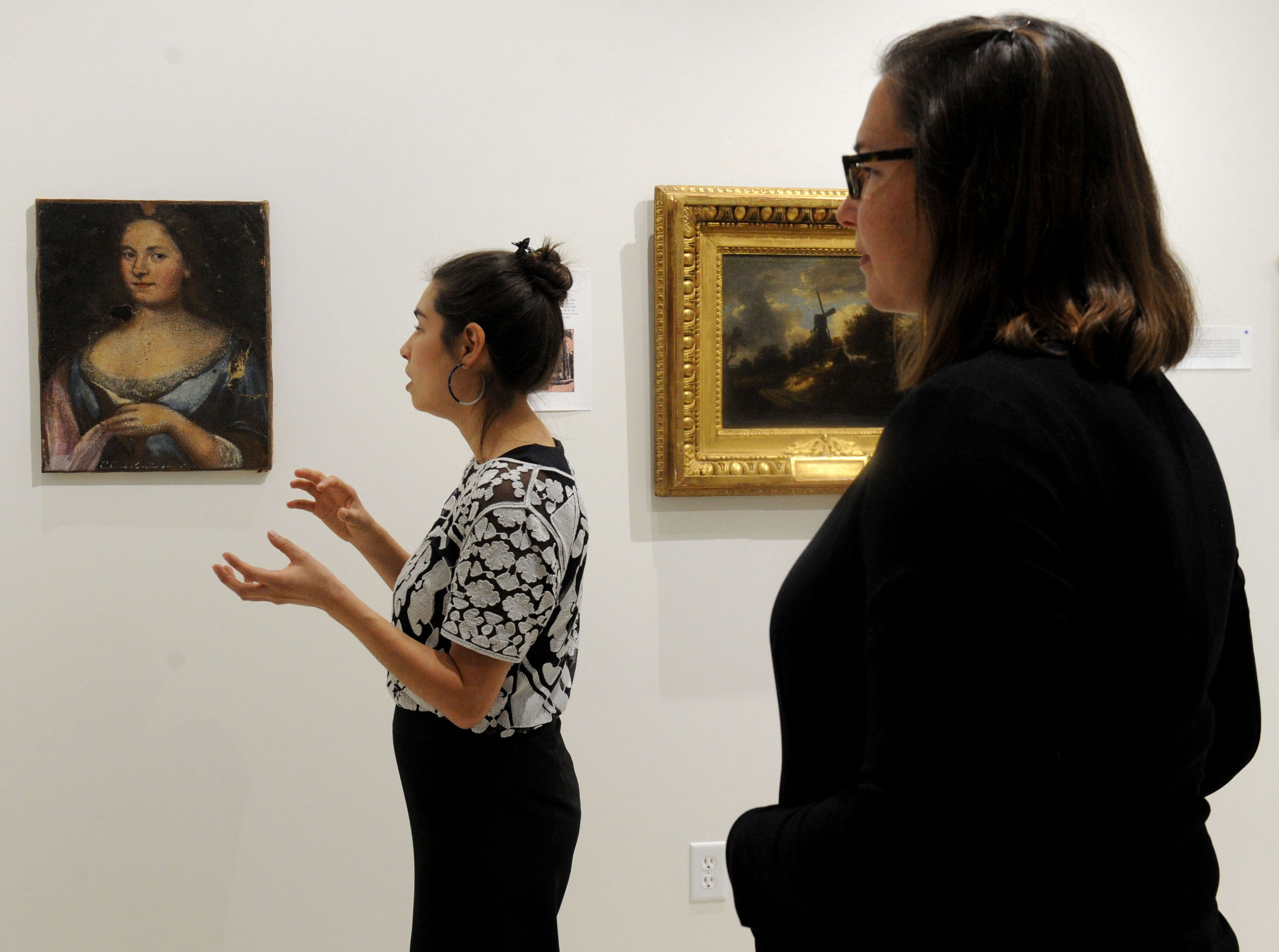 """Rachel Schmid (left), curator of the William Rolland Gallery of Fine Art at California Lutheran University, and  Katherine Hoffman, the John Stauffer professor of analytical chemistry, look at a piece of art by an unknown artist from the 18th century. It is part of the """"Traces: Revealing Secrets in Art and History"""" exhibit."""