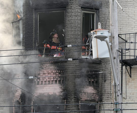 A Yonkers firefighter is pictured through a window as they battle a two alarm fire at 137 Hawthorne Avenue in the city, Jan. 12, 2019.