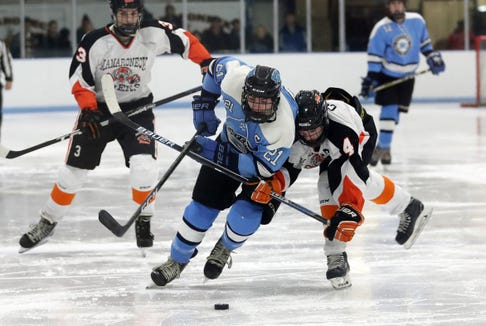 Suffern's Kyle Foresta (21) tries to break away from Mamaroneck's Thomas Conley (4) during hockey action at Hommocks Park Ice Rick in Mamaroneck Jan. 11, 2019. The two teams played to a 2-2 tie.