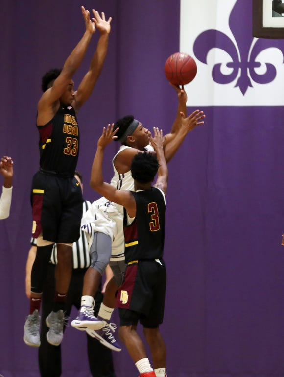 New Rochelle's Omari Walker (4) drives to the basket in front of MountVernon's Orlando Dawkins (33) and Charles Lovett (3) during boys basketball action at New Rochelle High School Jan. 12, 2019.