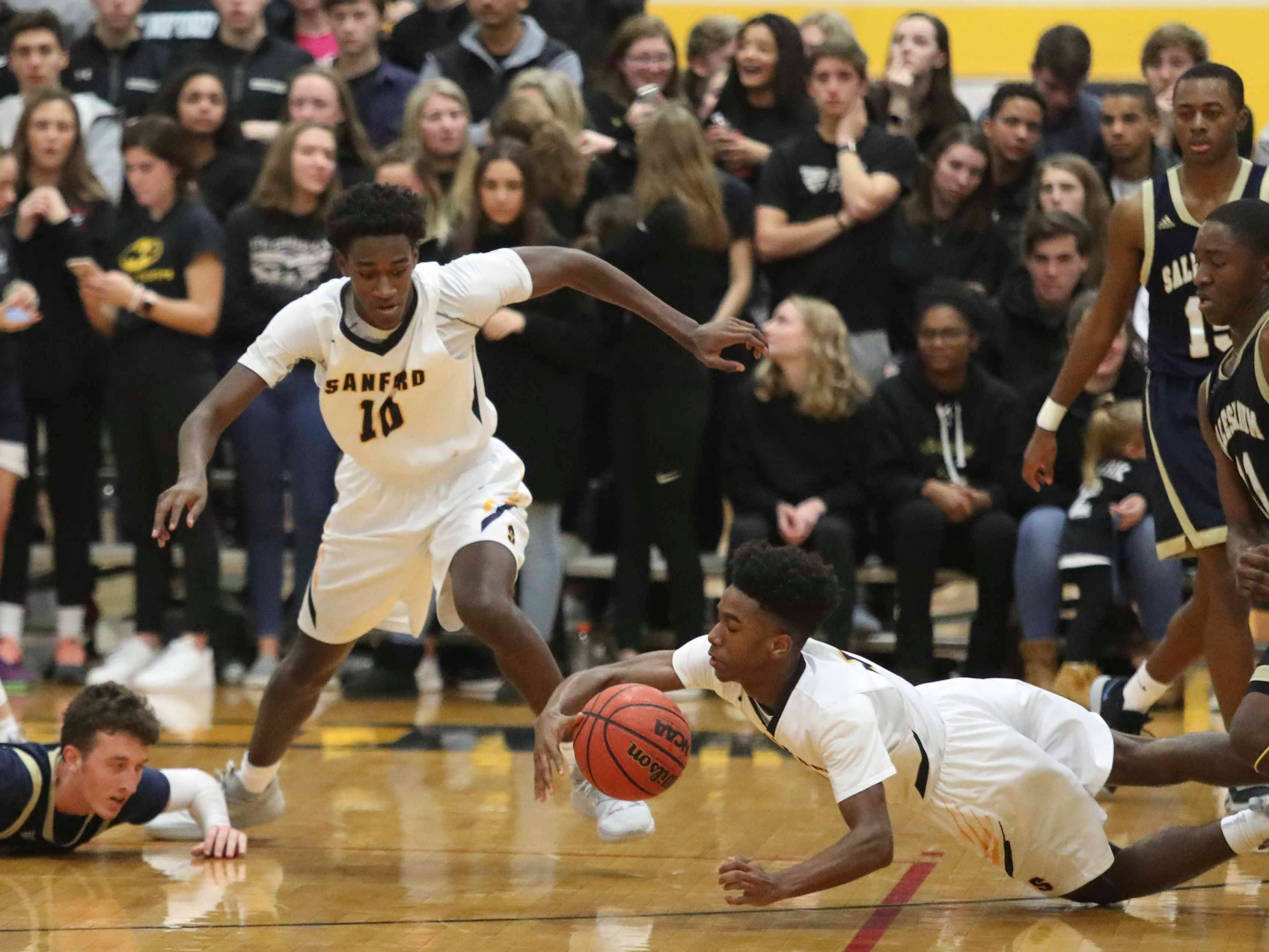 Sanford's Nasir Cowan snags a loose ball in front of teammate Devin Harris (10) and Salesianum's Jack Brown (bottom left) during the Warriors' 65-47 win at home Friday.