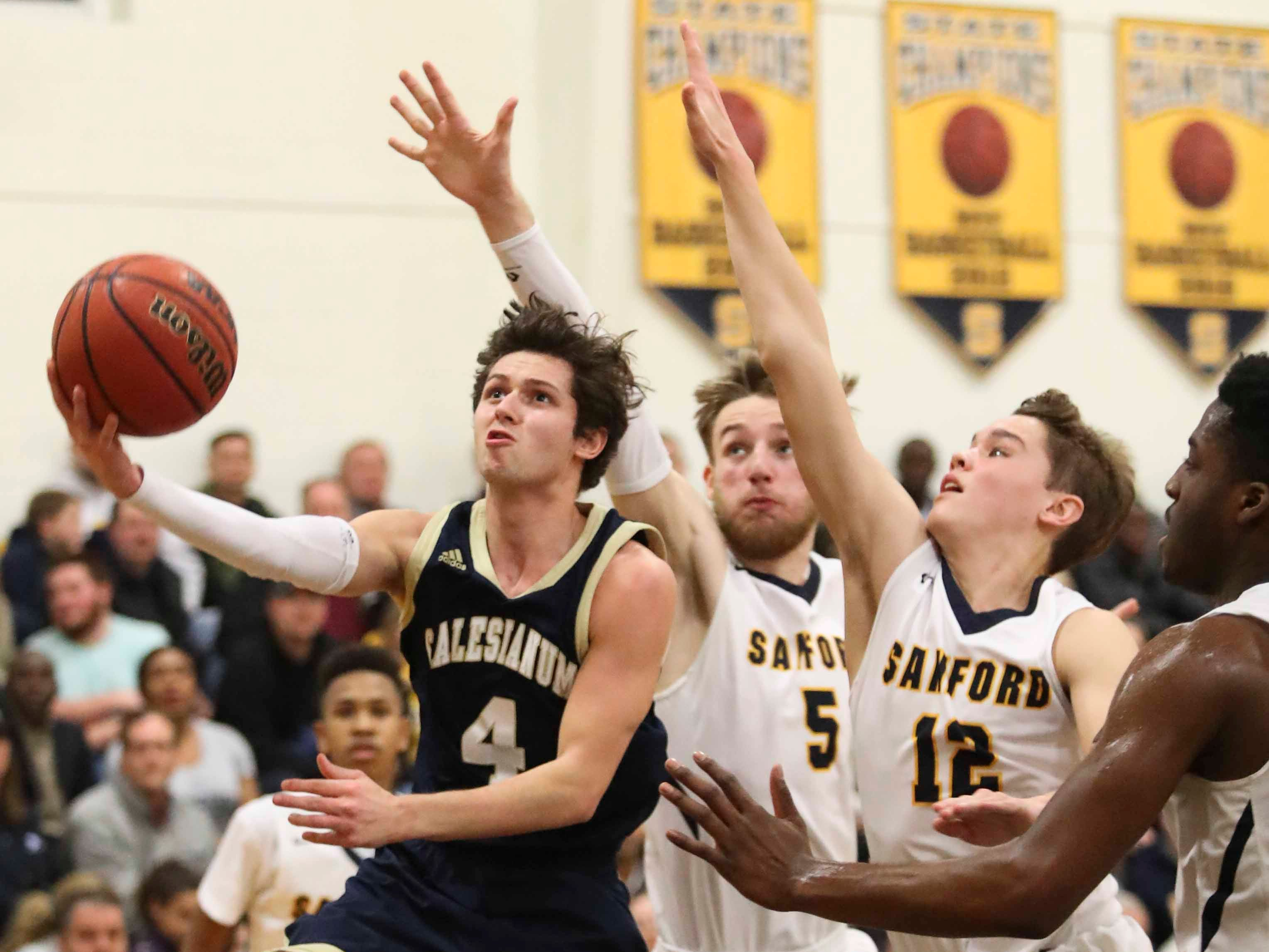 Salesianum's Max Ferrante drives against Sanford's Ryan McKeon (5) and Brandon Dwyer during the Warriors' 65-47 win at home Friday.
