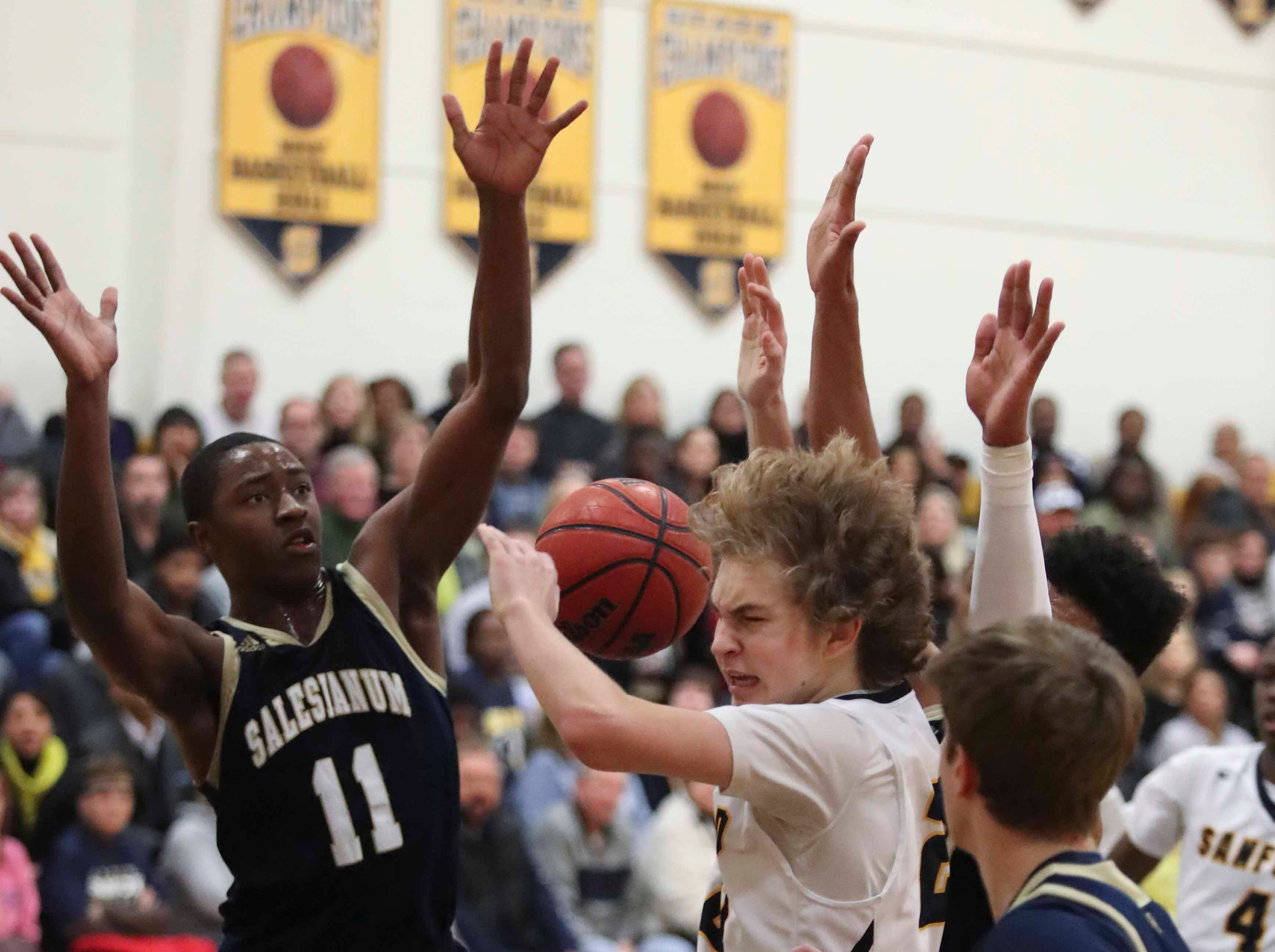 Sanford's Carter Ruby goes to the basket against Salesianum's Darnell Vaughan (left) and Thomas Montooth during the Warriors' 65-47 win at home Friday.
