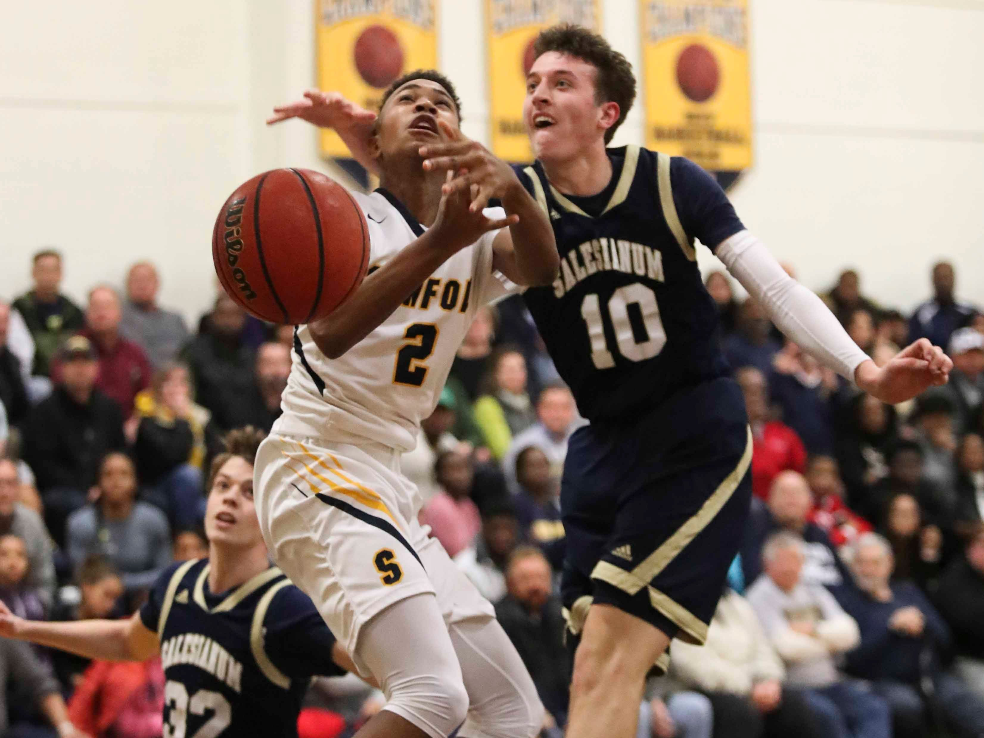 Sanford's Corey Perkins (left) is fouled by Salesianum's Jack Brown during the Warriors' 65-47 win at home Friday.