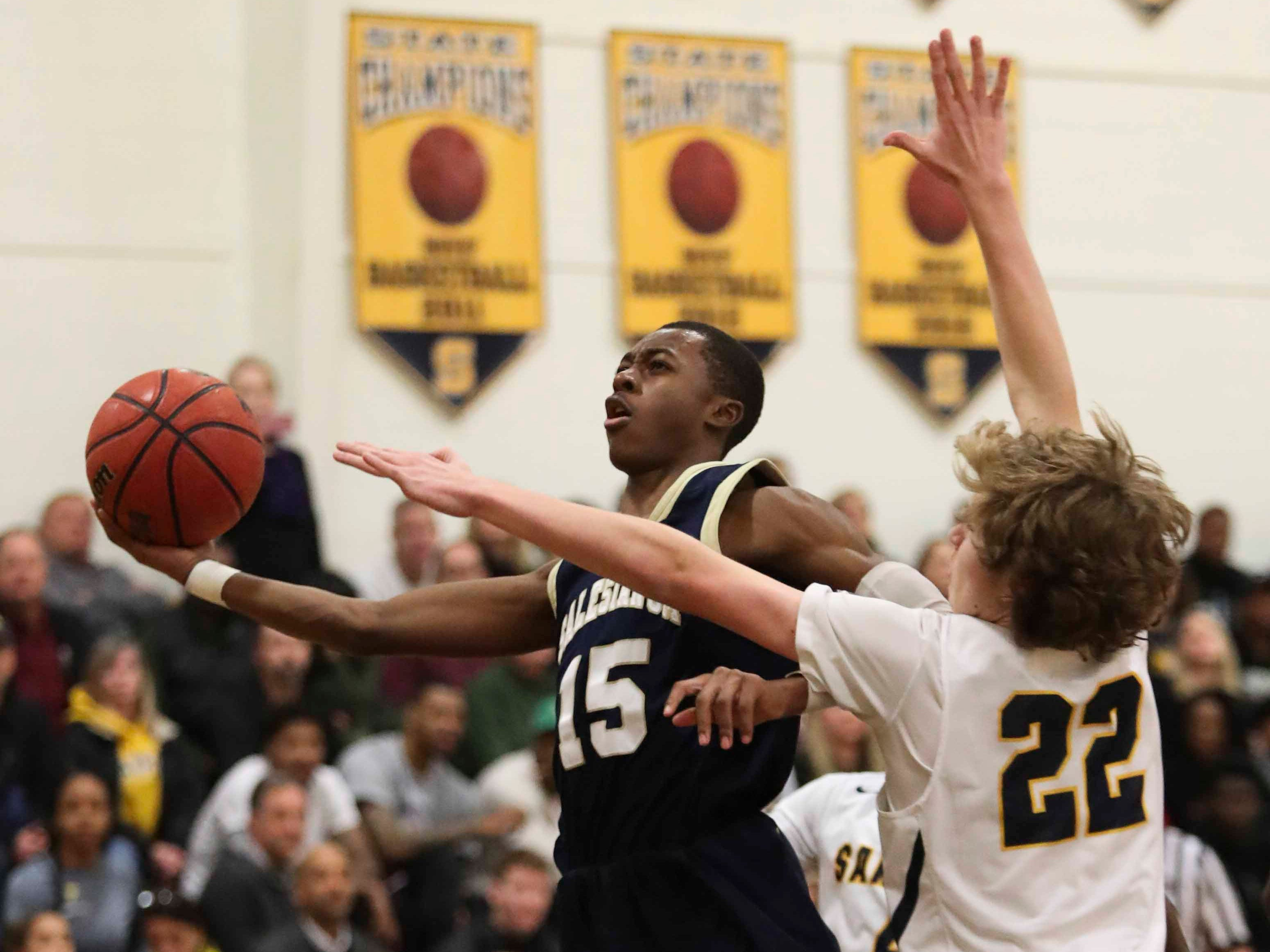 Salesianum's Rasheed Caulk goes to the basket against Sanford's Carter Ruby in the Warriors' 65-47 win at home Friday.