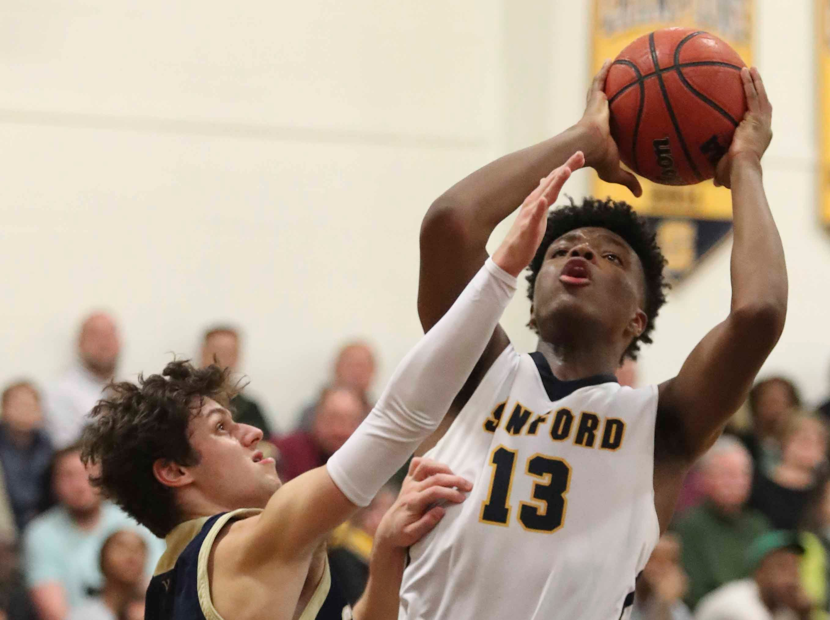Salesianum's Max Ferrante (left) and defends Sanford's Jyare Davis during the Warriors' 65-47 win at home Friday.