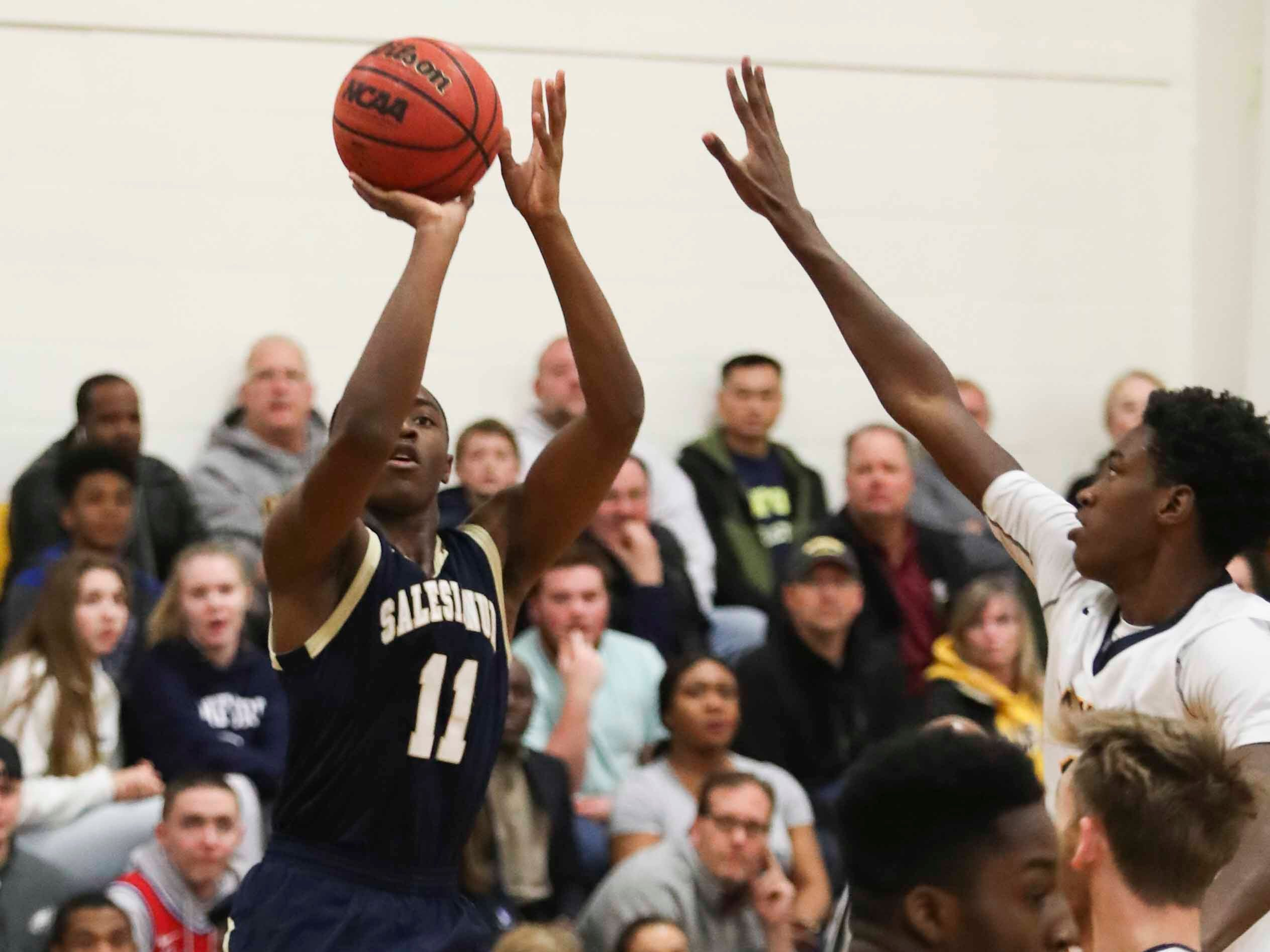 Salesianum's Darnell Vaughan shoots against Sanford's Devin Harris during the Warriors' 65-47 win at home Friday.