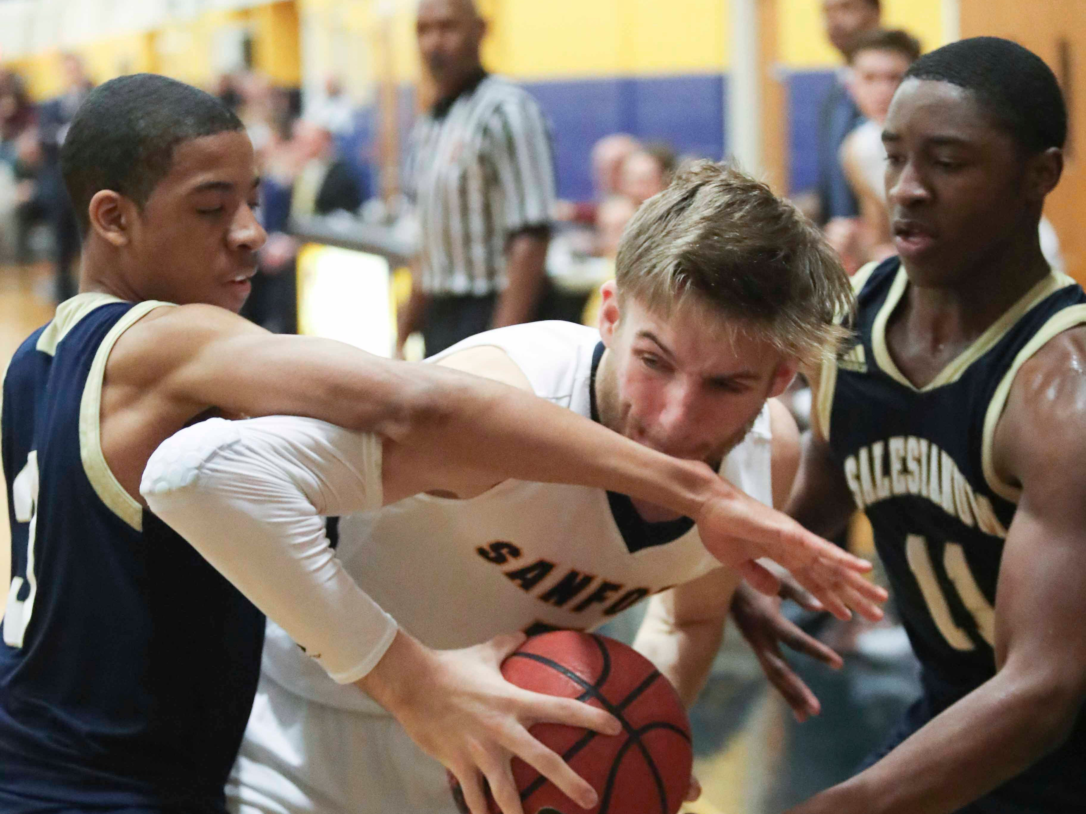 Sanford's Ryan McKeon tries to work out of the defense of Salesianum's Charles Parson (left) and Darnell Vaughan during the Warriors' 65-47 win at home Friday.