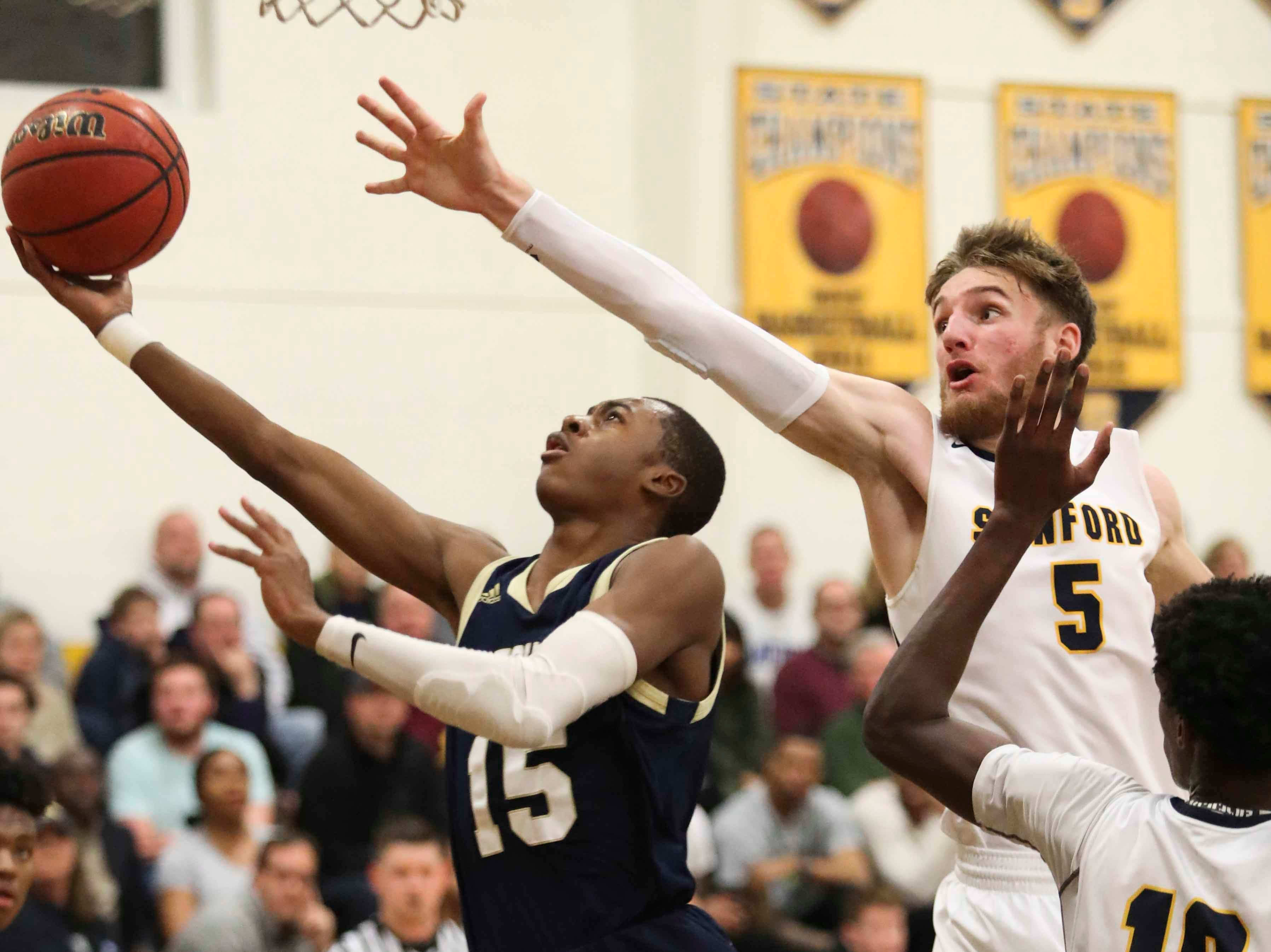Sanford's Rasheen Caulk (left) goes to the basket as Sanford's Ryan McKeon defends during the Warriors' 65-47 win at home Friday.
