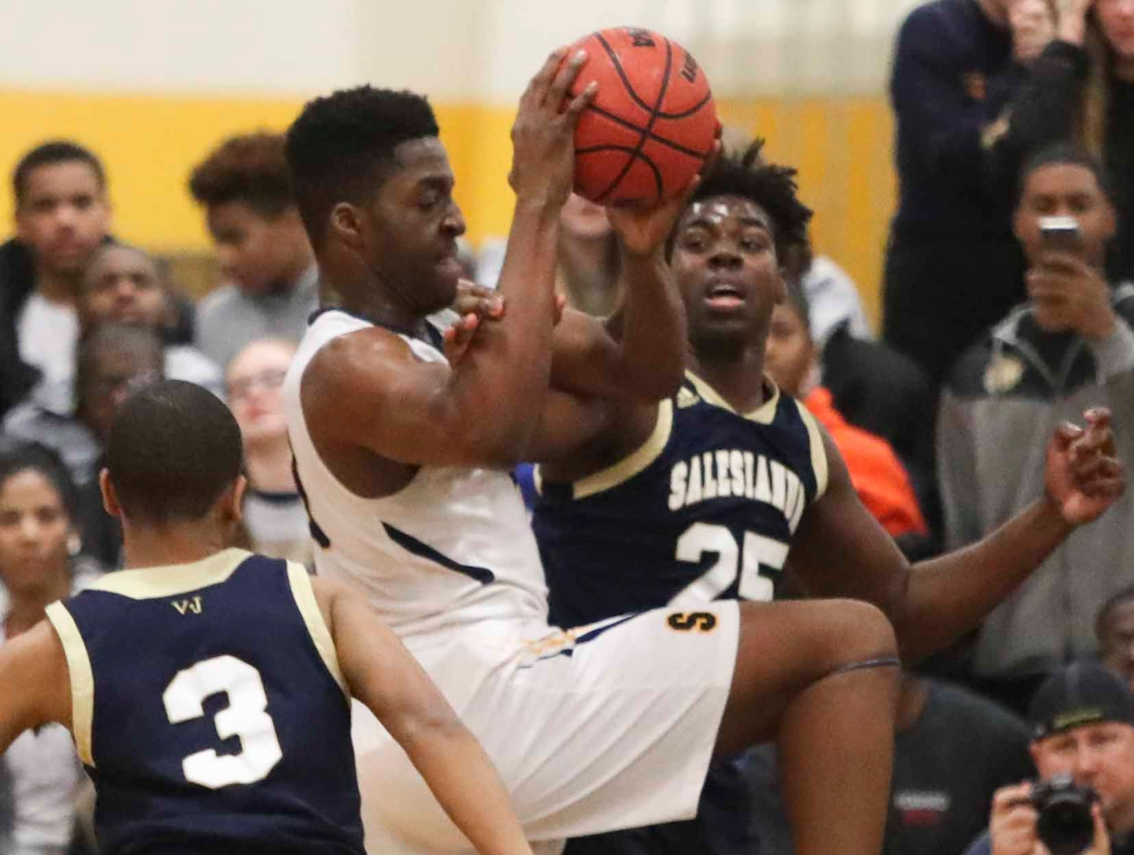 Sanford's Nnanna Njoku moves between Salesianum's Charles Parson (left) and James Yelbert during the Warriors' 65-47 win at home Friday.