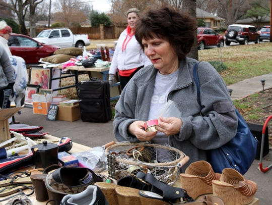 Sherian Del Toro browses through the items setup on a table Saturday, Jan. 12, 2019, at the Federal Employees' Government Shutdown Yard Sale on Nassau Drive.