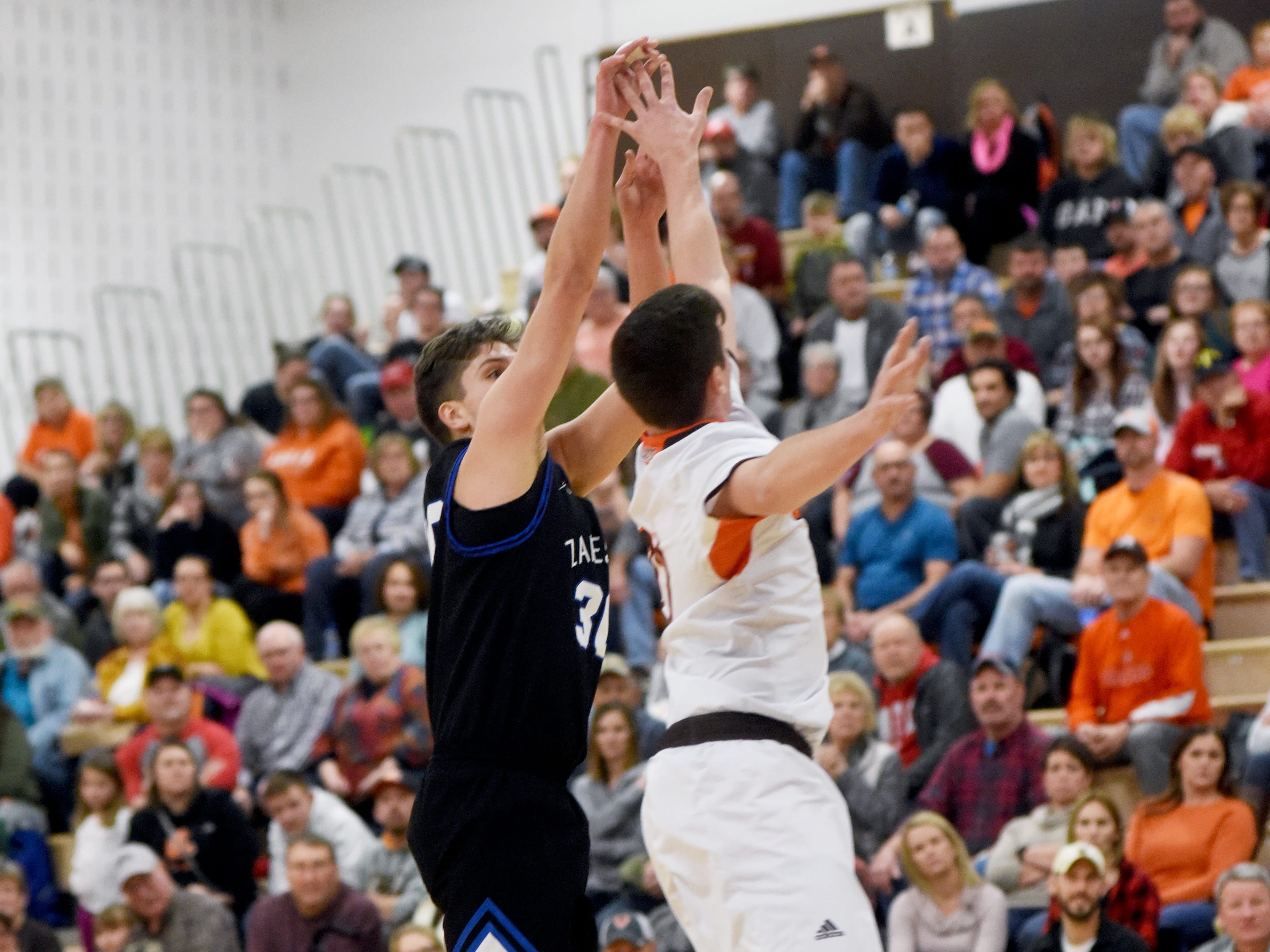 Cobe Curry shoots a 3 over Davis Black during Zanesville's 60-55 loss to Meadowbrook on Friday in Byesville.