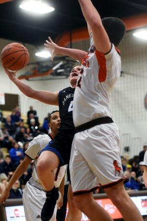 Zanesville's Clayton Foreman is met in the lane by Meadowbrook's Davis Black during the Blue Devils' 60-55 loss on Friday night in Byesville.