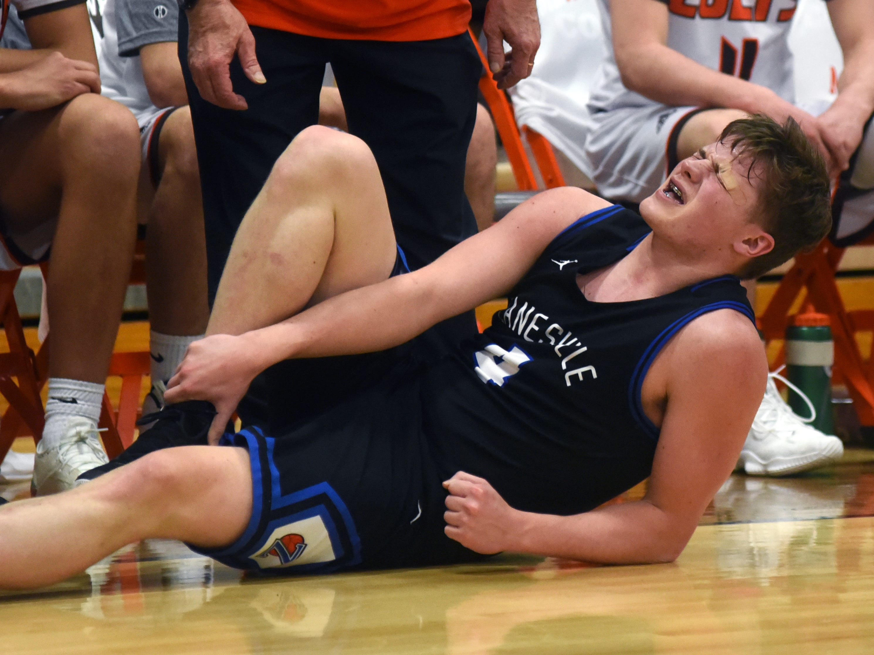 Clayton Foreman winces in pain after injuring his right ankle during the first half of Zanesville's 60-55 loss to Meadowbrook on Friday in Byesville.