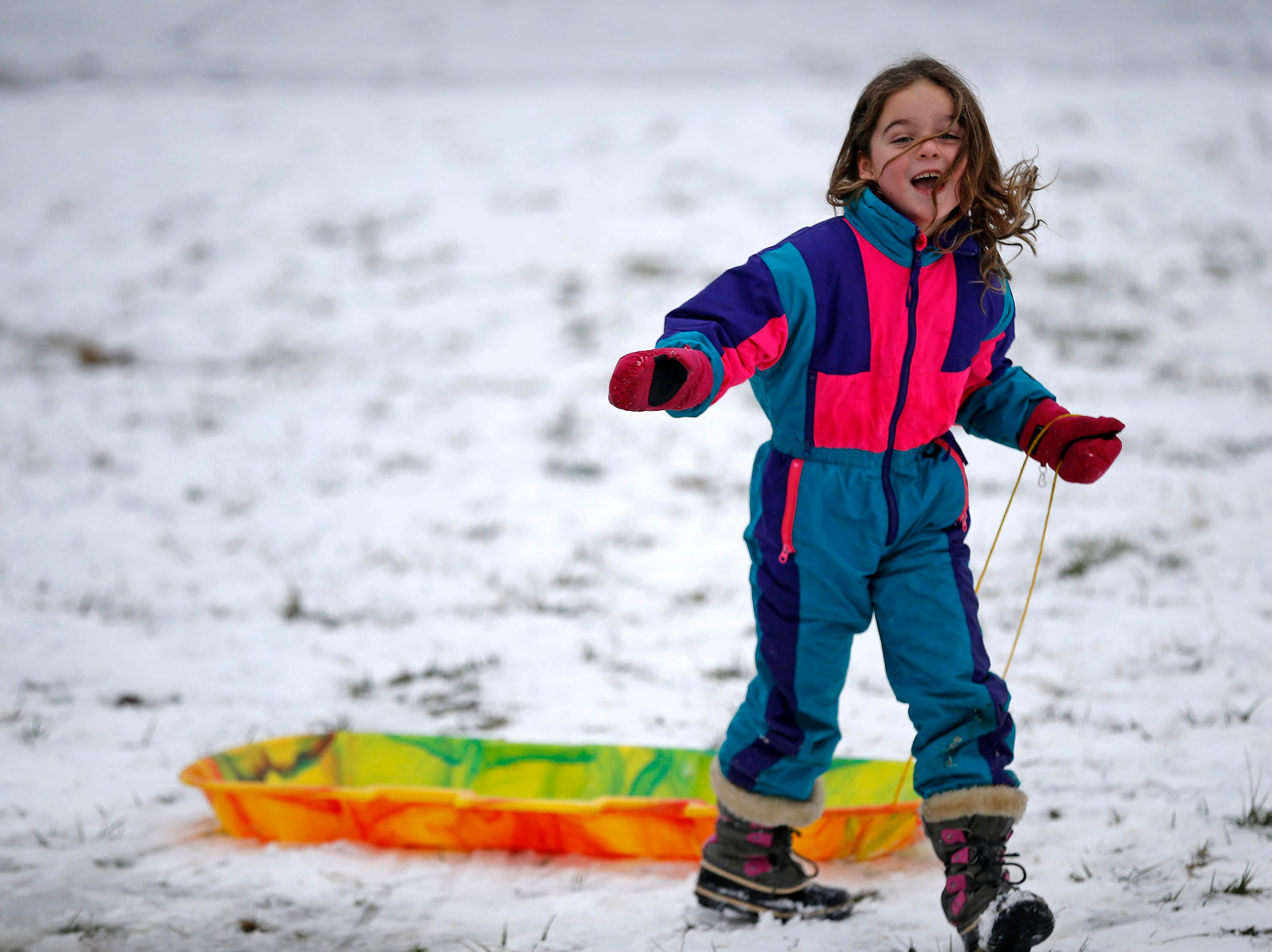 Becca Ryan, 7, of Columbia Tusculum, laughs after turning up hill to take another sled ride at Ault Park in the Hyde Park neighborhood of Cincinnati on Saturday, Jan. 12, 2019. A winter storm warning remained in effect until 7 A.M. Sunday after the region experienced the first snowfall of 2019.
