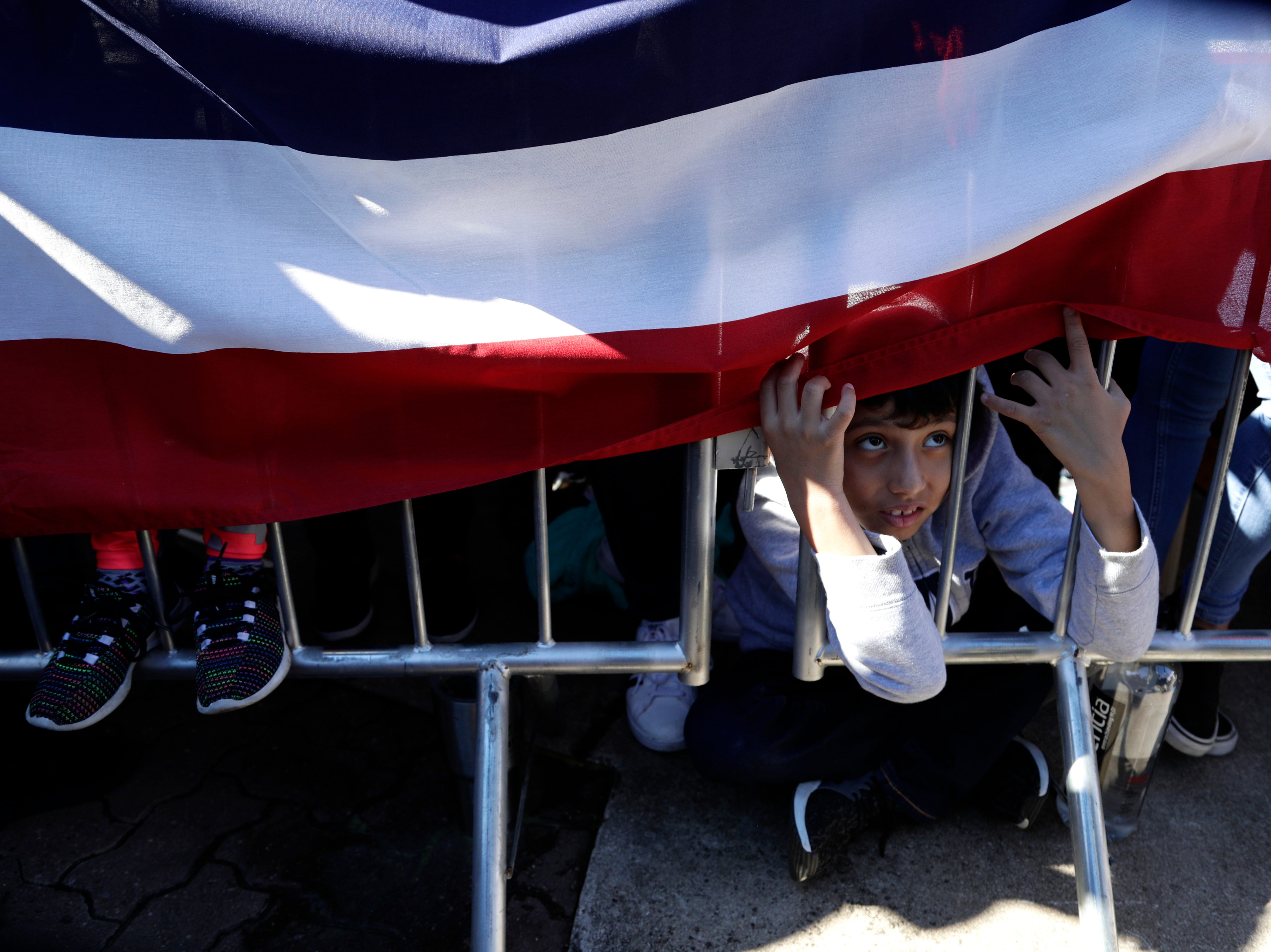 A young boy peeks under a banner as he watches Julian Castro make his announcement.