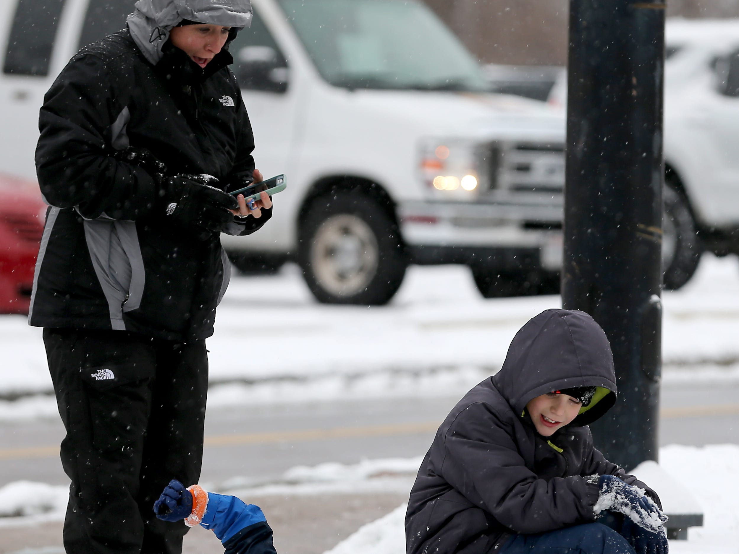 Two children play in the snow before the procession for Colerain Township Police Officer Dale Woods passes through North College Hill along Galbraith Road, Saturday, Jan. 12, 2019, in North College Hill, Ohio. Woods, 46, who died Monday after being hit by a pickup truck Jan. 4 while working at the scene of a crash.