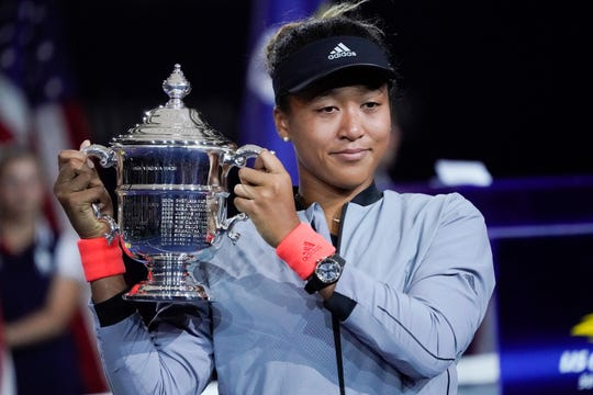 Naomi Osaka holds the 2018 US Open trophy after beating Serena Williams in the final.