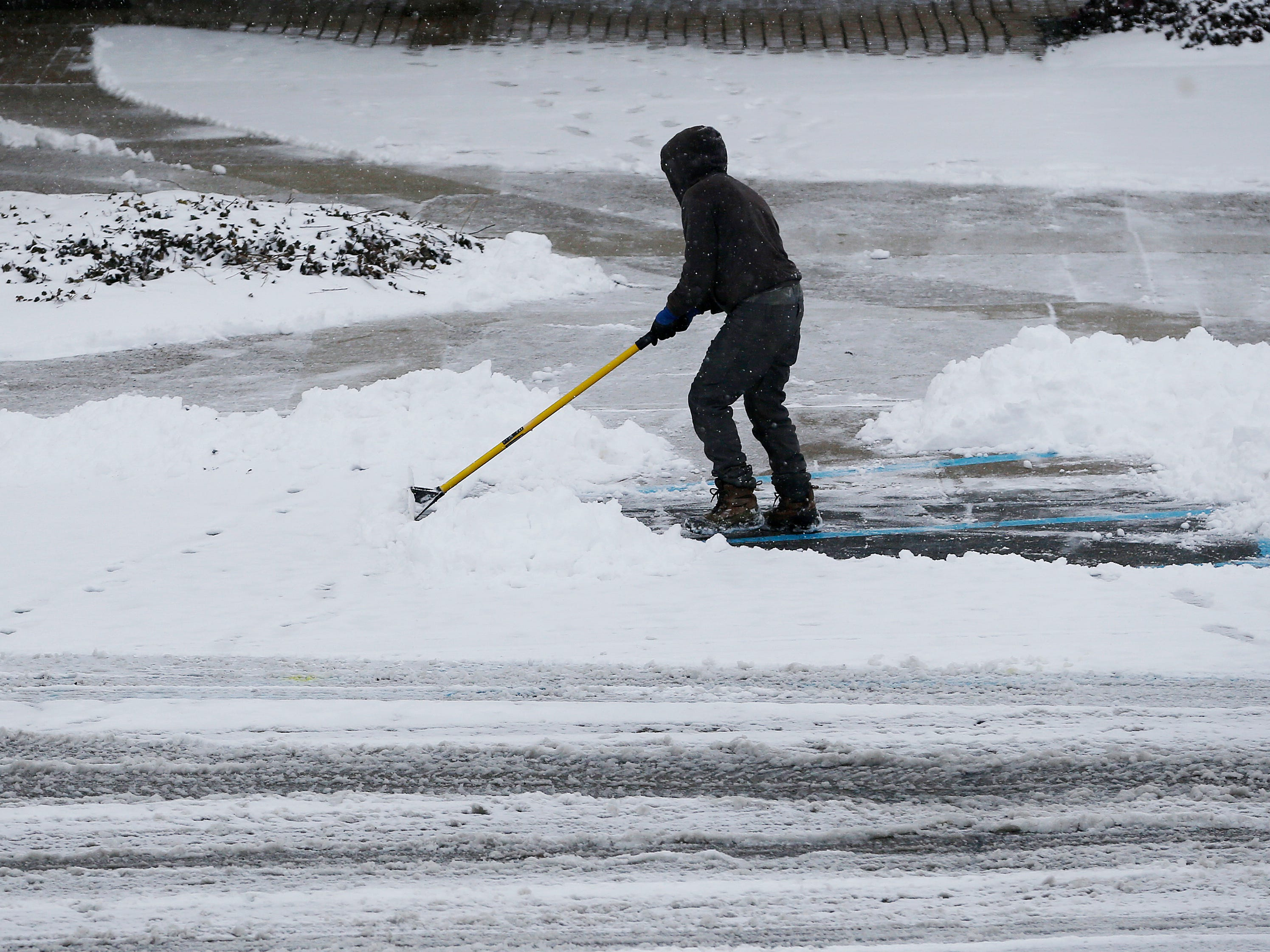 A man shovels as snow continues to fall in Colerain Township, a suburb Cincinnati Saturday Jan. 12, 2019. The National Weather Service cautioned that the accumulation will lead to hazardous travel in the area, recommending travelers stay home if possible until Sunday.