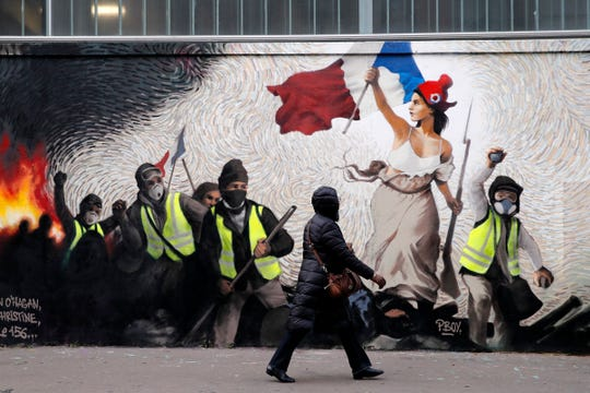 A woman passes by a mural by street artist PBOY depicting Yellow Vest (gilets jaunes) protestors inspired by a painting by Eugene Delacroix,