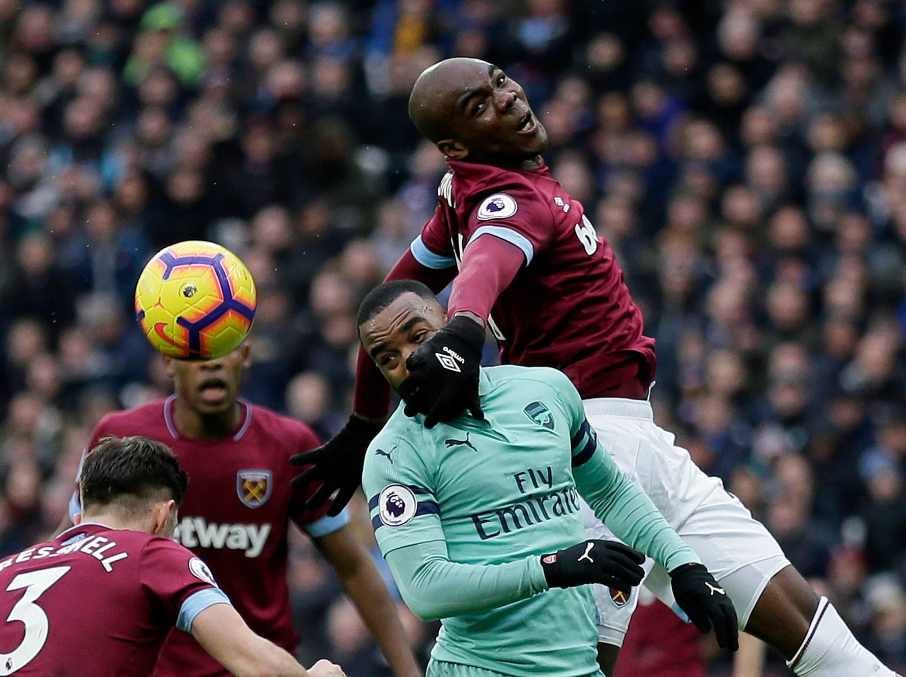 West Ham's Angelo Ogbonna jumps for the ball above Arsenal's Alexandre Lacazette.