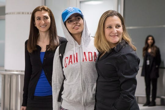 Rahaf Mohammed Alqunun, 18, center, stands with Canadian Minister of Foreign Affairs Chrystia Freeland, right, as she arrives at Toronto Pearson International Airport, on Jan.12, 2019.