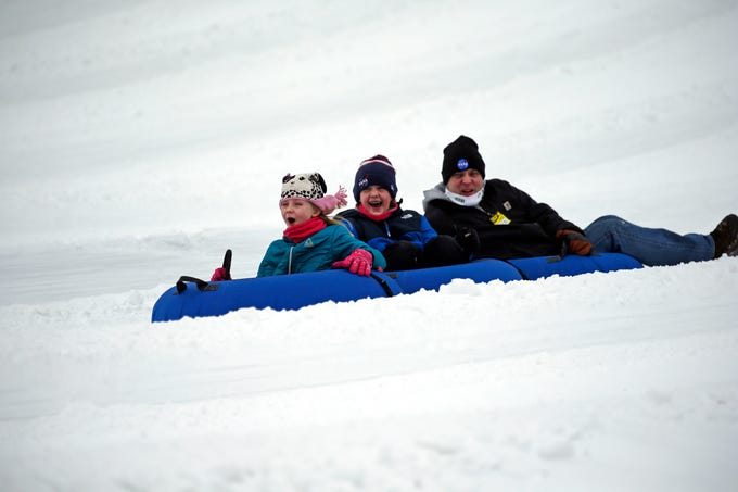 Summer and Autumn Scott of Neshkoro laugh as they head down the hill with their father, Scott, as a mild winter day brings tubing fans to Nordic Mountain Sunday, Jan. 13, 2019, near Wild Rose, Wis.