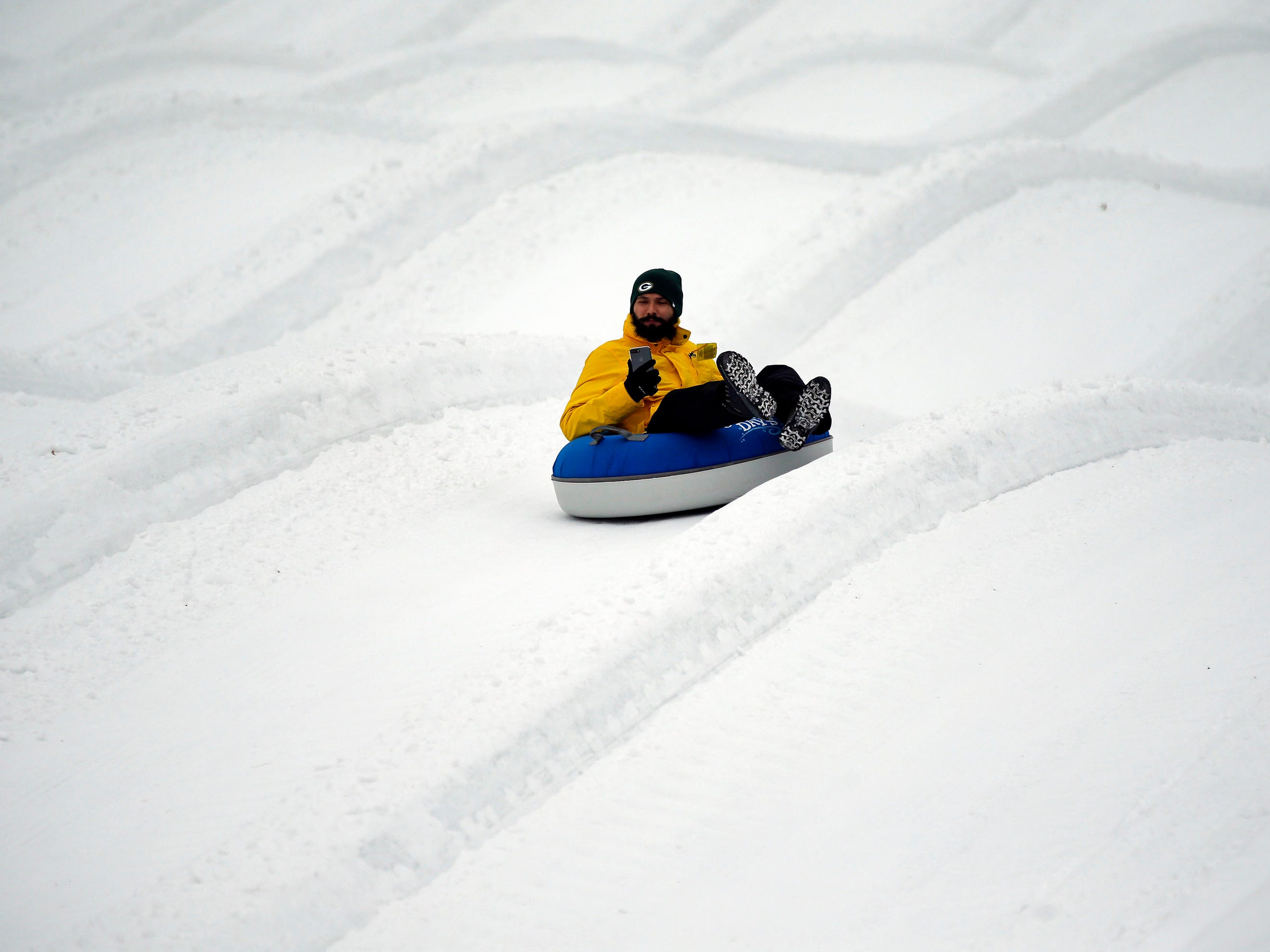 Andre Shartener records his ride as a mild winter day brings tubing fans to Nordic Mountain Sunday, January 13, 2019, near Wild Rose, Wis.