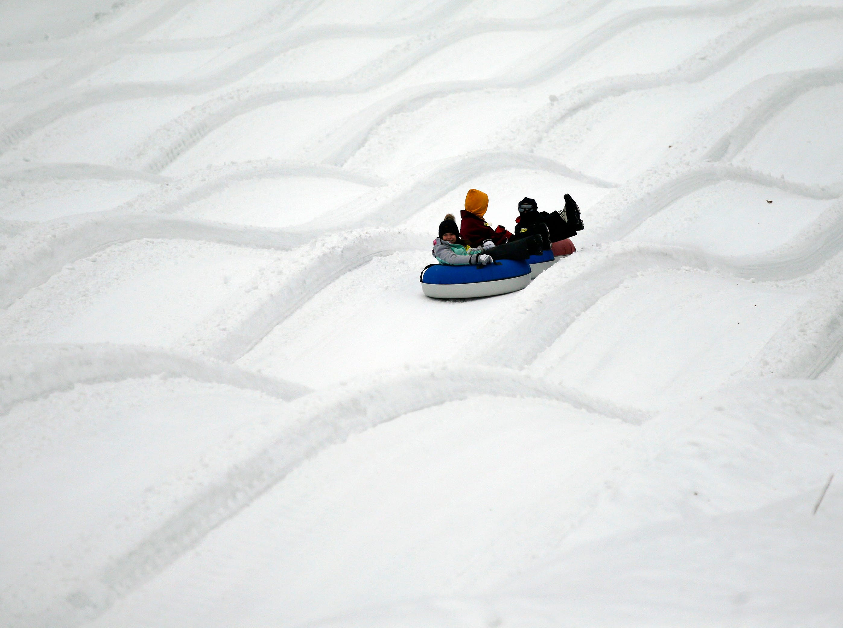 Jennifer Kohnke of Montello and her children Saydee and Klay make a run as a mild winter day brings tubing fans to Nordic Mountain Sunday, January 13, 2019, near Wild Rose, Wis.