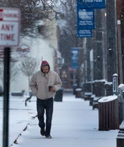 A lone walker trudges down Washington Ave in Toms River as a light snow falls Sunday morning.