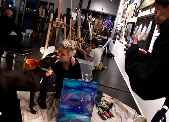 Ruthie Swedlund gets a smooch from an appreciative four-legged fan while competing in the acrylic paint-off inside the Center for Contemporary Arts on Thursday.